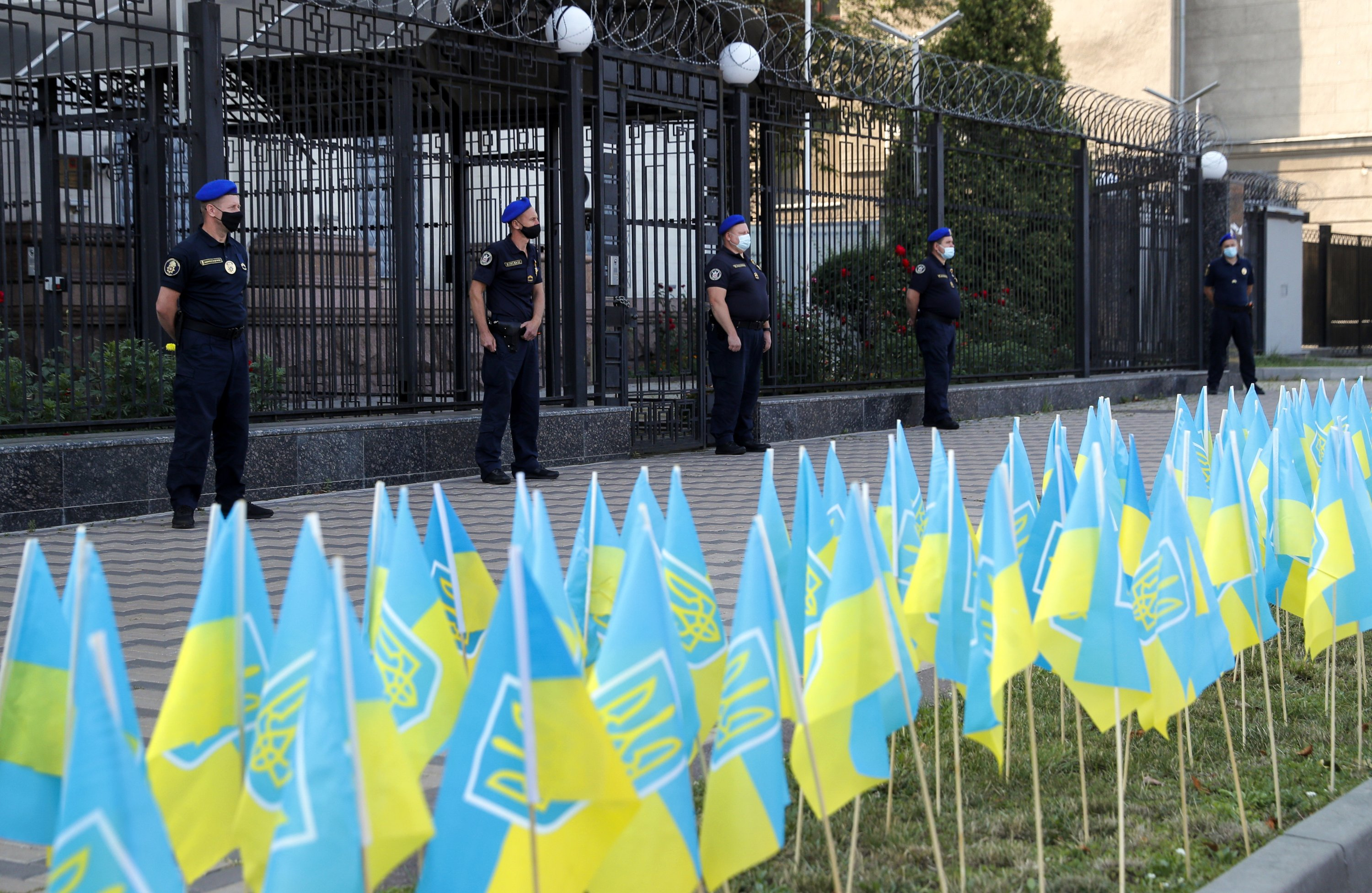Embassy guards watch 150 Ukrainian flags placed in memory of the estimated 15,000 people killed in the Eastern Ukraine conflict, in front of the Russian embassy building in Kyiv, Ukraine, Aug. 23, 2021. (EPA Photo)