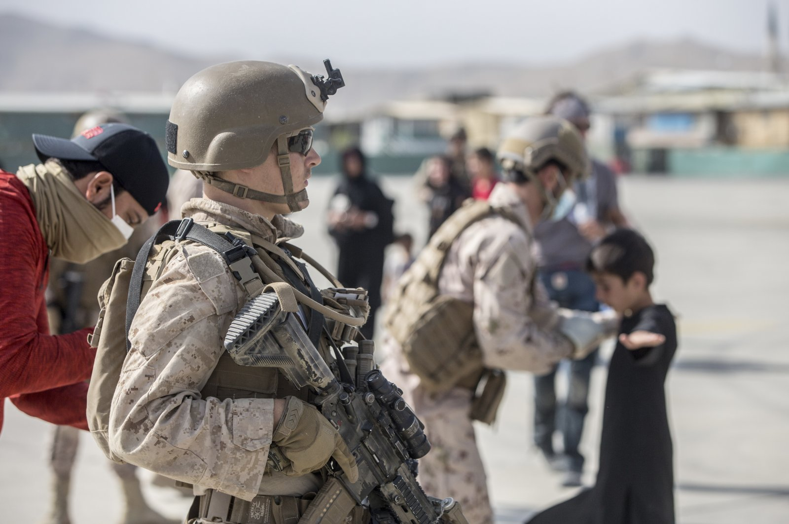 A Marine with Special Purpose Marine Air-Ground Task Force-Crisis Response-Central Command (SPMAGTF-CR-CC) provides assistance during an evacuation at Hamid Karzai International Airport in Kabul, Afghanistan, Aug. 21, 2021. (AP Photo)