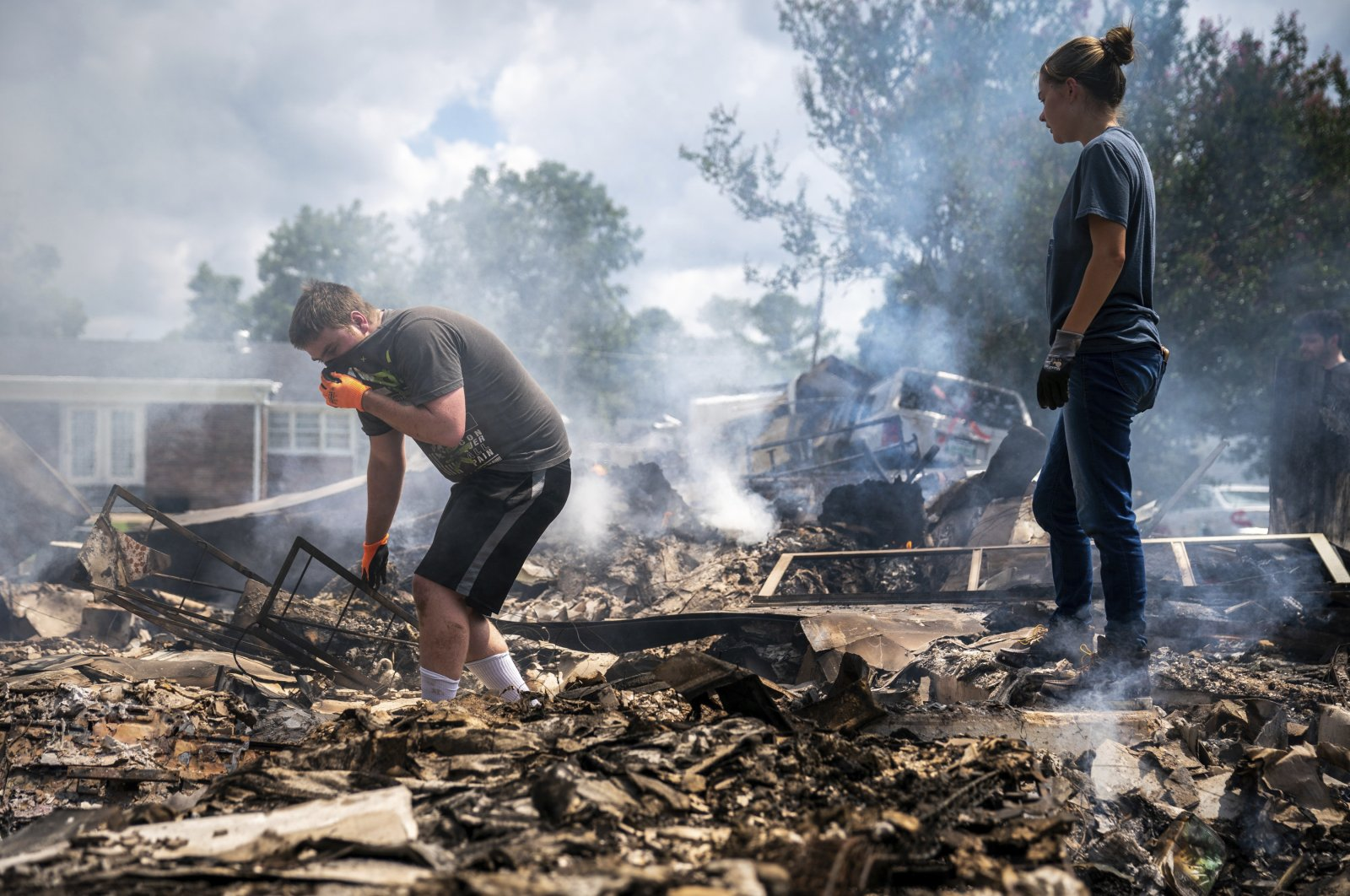 Josh Whitlock and Stacy Mathieson look through what is left of their home after it burned following flooding in Waverly, Tenn., Aug. 22, 2021. (AP Photo)