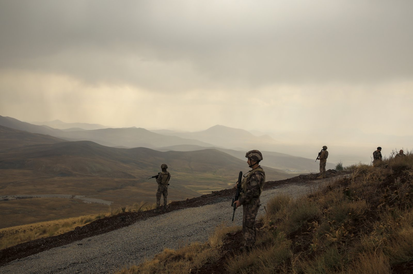 Turkish soldiers stand guard near the wall that separates Turkey and Iran, in Van Province, Turkey, Aug. 21, 2021. (AP Photo)