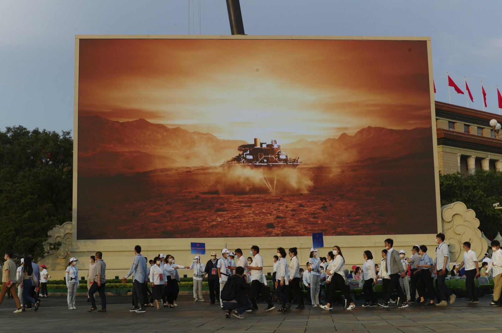 Attendees at a ceremony to mark the 100th anniversary of the founding of the ruling Chinese Communist Party pass by a screen depicting China's Mars spacecraft with its rover landing, in Beijing, China, July 1, 2021. (AP Photo)