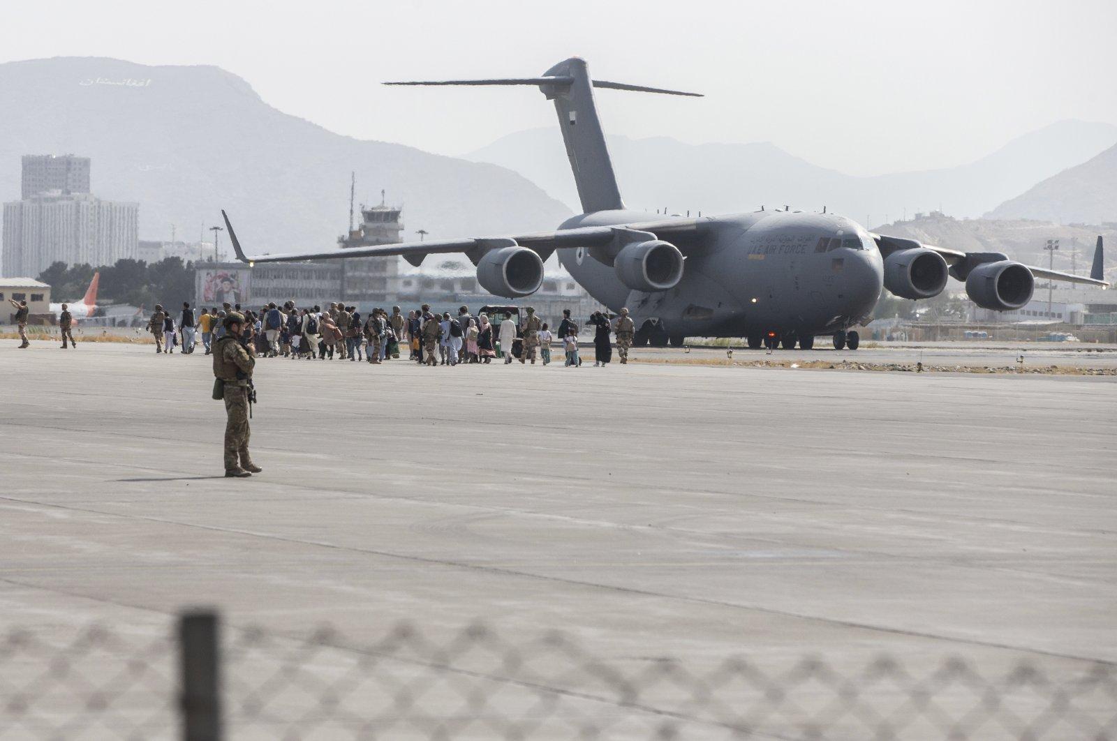 In this photo provided by the U.S. Marine Corps, evacuees load onto a U.S. Air Force Boeing C-17 Globemaster III during an evacuation at Kabul Hamid Karzai International Airport, Kabul, Afghanistan, Aug. 21, 2021. (Sgt. Samuel Ruiz/U.S. Marine Corps via AP)