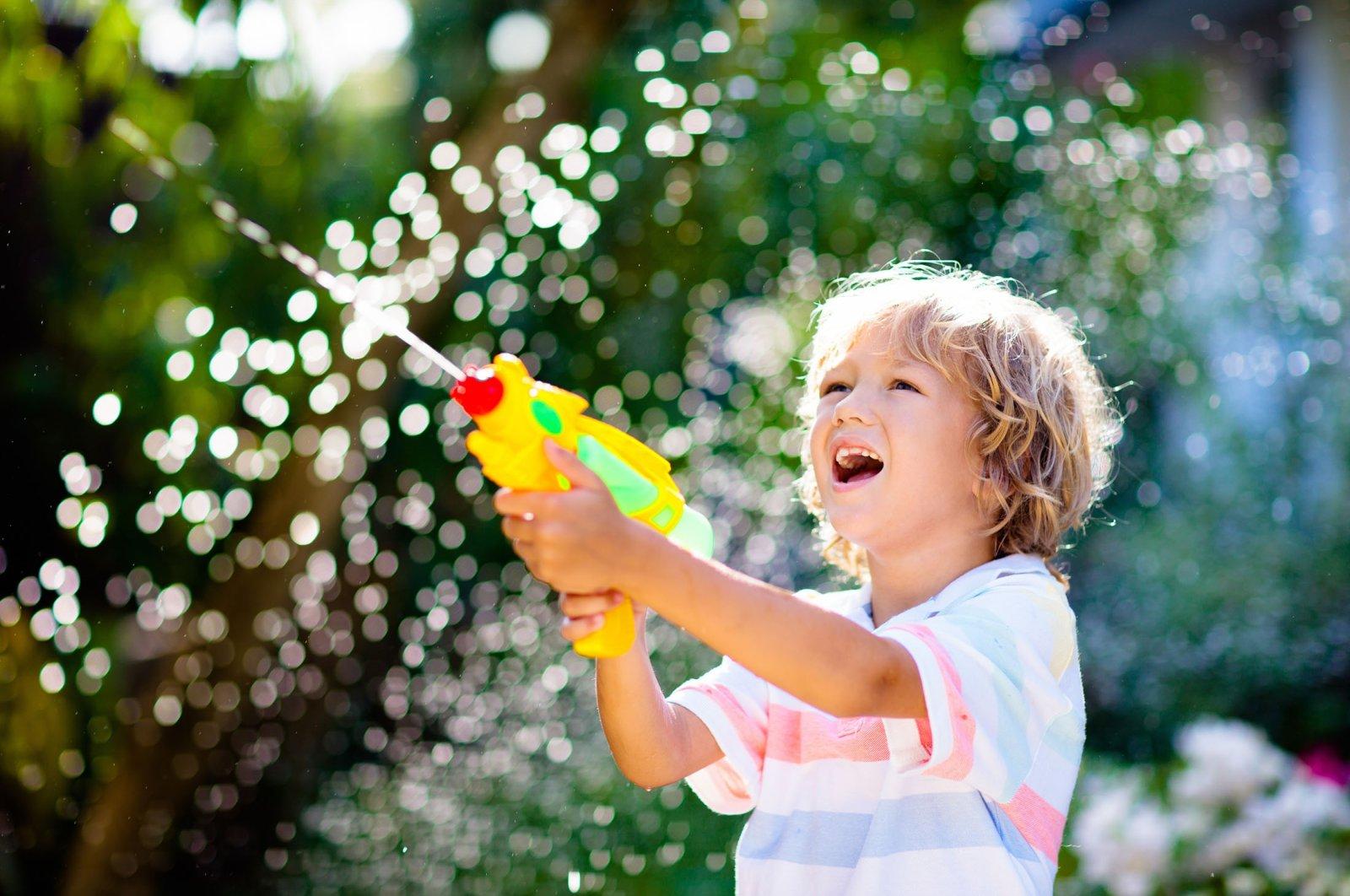 Kids play with water gun toy in garden. (Shutterstock Photo)