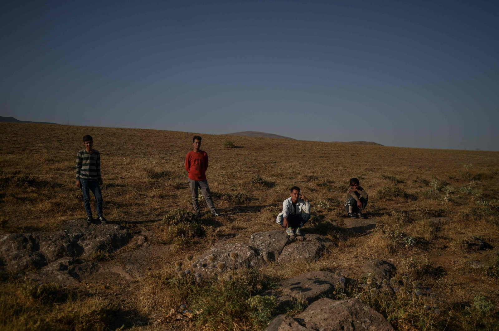 Afghan migrants rest while waiting for transport from smugglers after crossing the Iran-Turkish border, Tatvan, on the western shores of Lake Van, eastern Turkey, on Aug. 15, 2021. (Ozan KÖSE / AFP)
