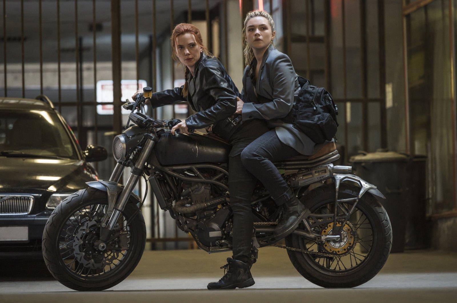 "Scarlett Johansson (L) rides a motorcycle with Florence Pugh in a scene from Marvel superhero film ""Black Widow."" (Disney via AP)"