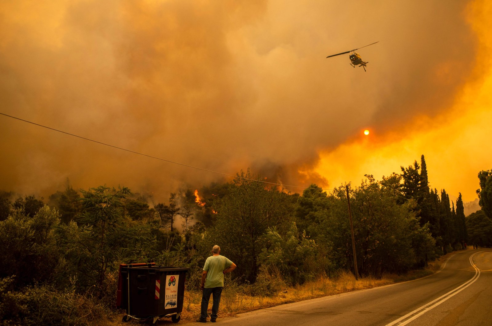 A man watches a helicopter during a fire in the village of Villa, northwest of Athens, Greece, Aug. 18, 2021. (AFP Photo)