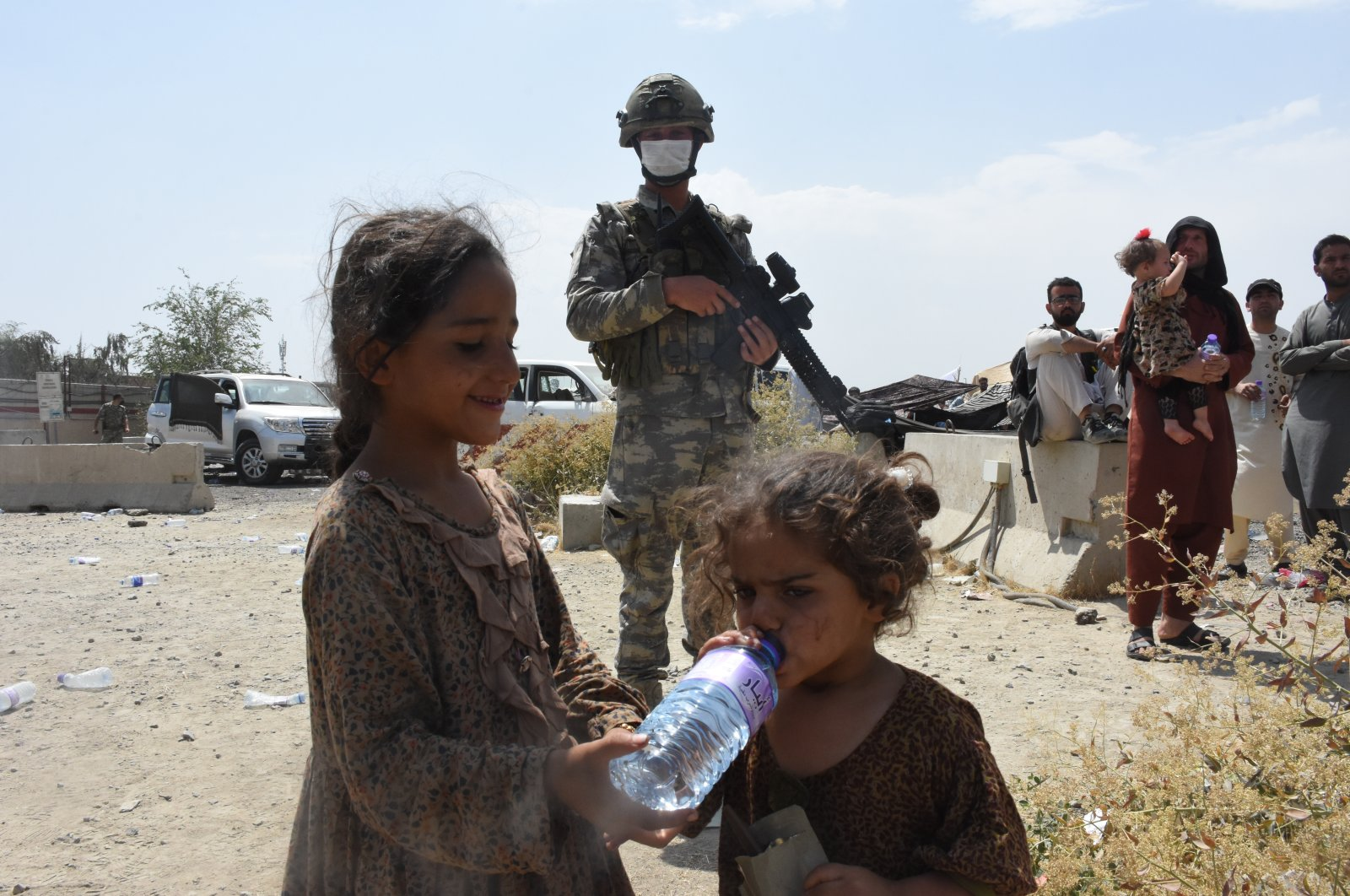 Afghan children drink water provided by Turkish soldiers near Kabul Hamid Karzai International Airport, Afghanistan, Aug. 22, 2021. (AA Photo)