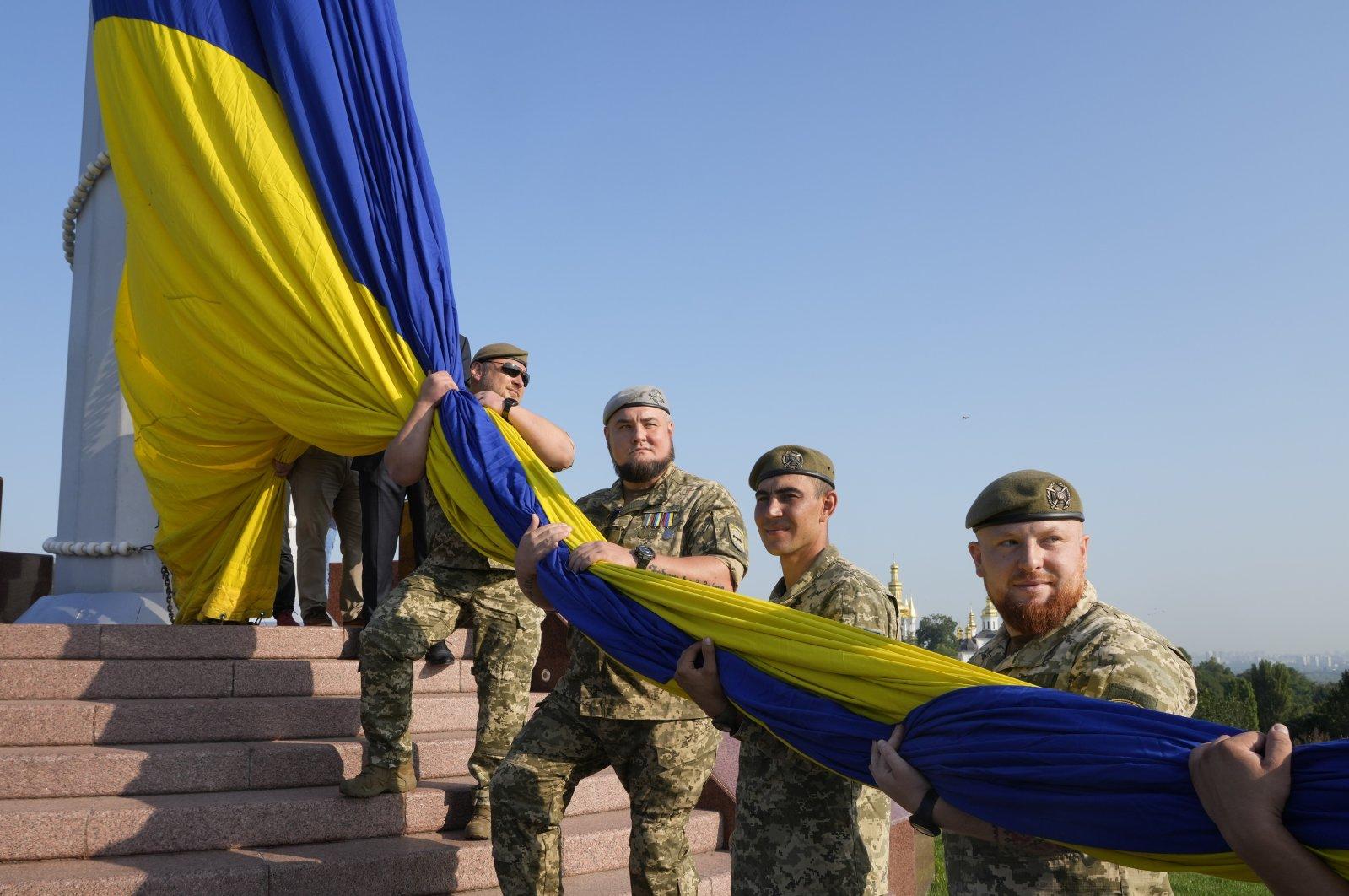 Army veterans raise Ukraine's state flag to mark the State Flag Day in Kyiv, Ukraine, Aug. 23, 2021. (AP Photo)