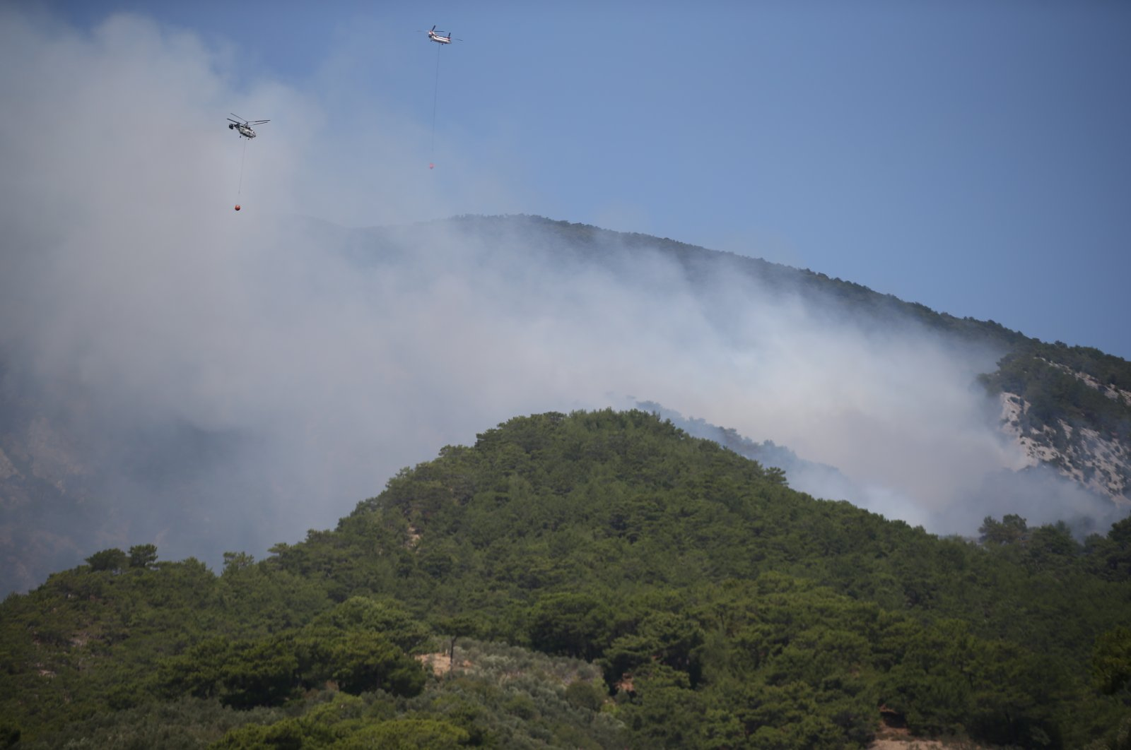 Helicopters and airplanes dump water on burning forest, in Edremit, Balıkesir, western Turkey, Aug. 23, 2021. (AA PHOTO)