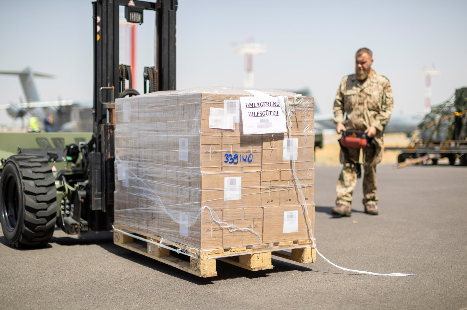 A soldier loads aid supplies destined for Afghanistan on a transport aircraft of the German Air Force at Tashkent airport, Uzbekistan, Aug. 22, 2021. (Handout from German Air Force via EPA)