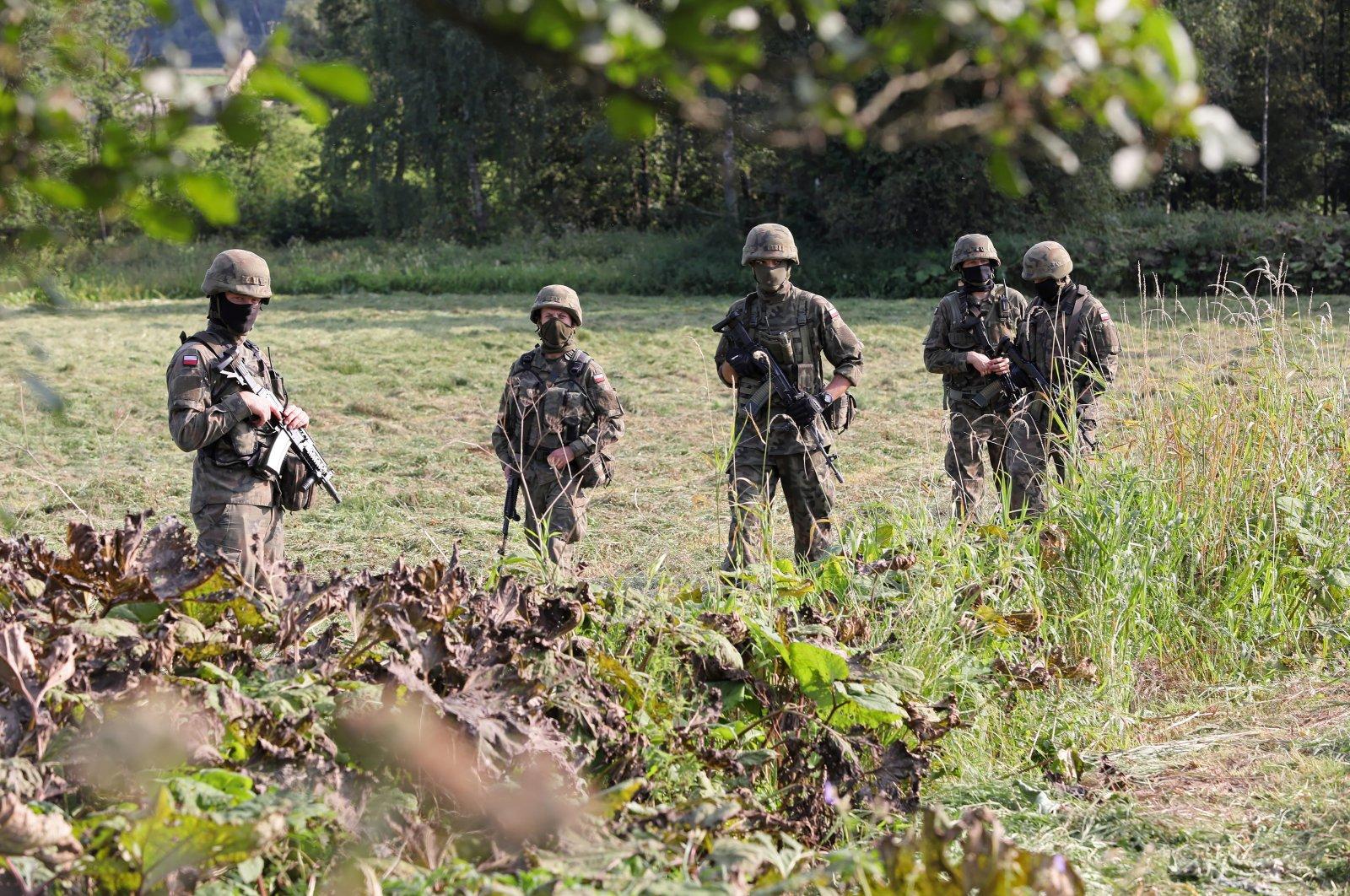 Polish border guard and the army near the town of Usnarz Górny, Poland, Aug. 22, 2021. (EPA Photo)