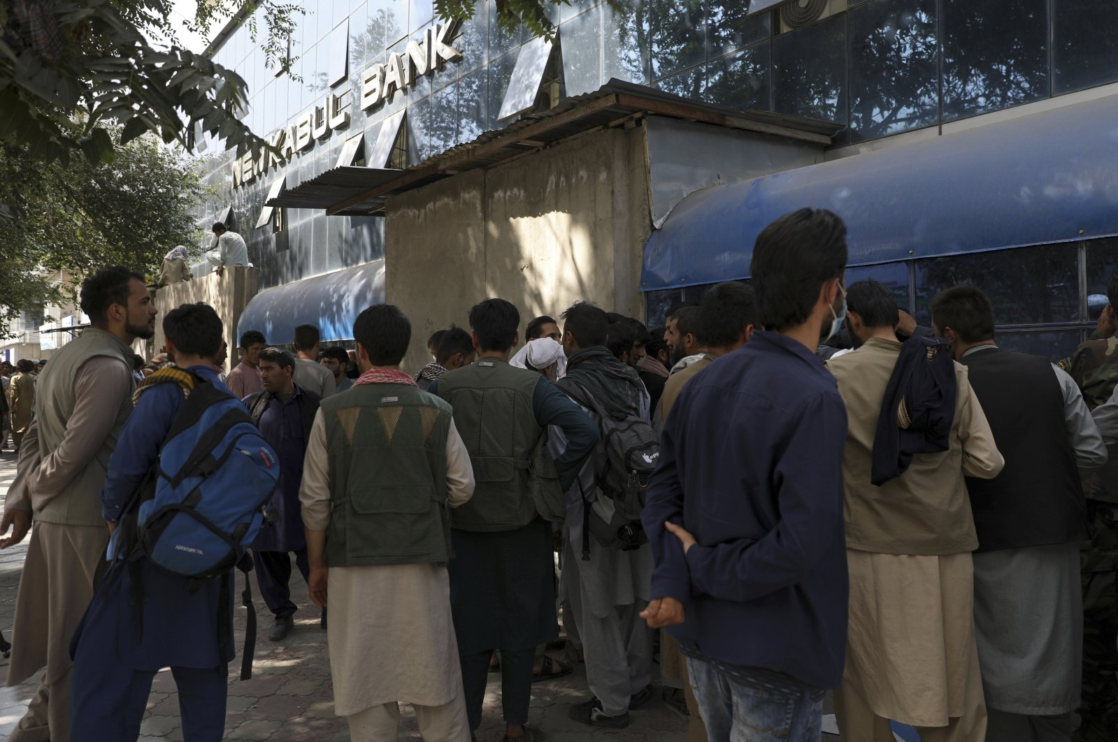 Afghans wait in long lines for hours to try to withdraw money, in front of Kabul Bank, in Kabul, Afghanistan, Aug. 15, 2021. (AP Photo)