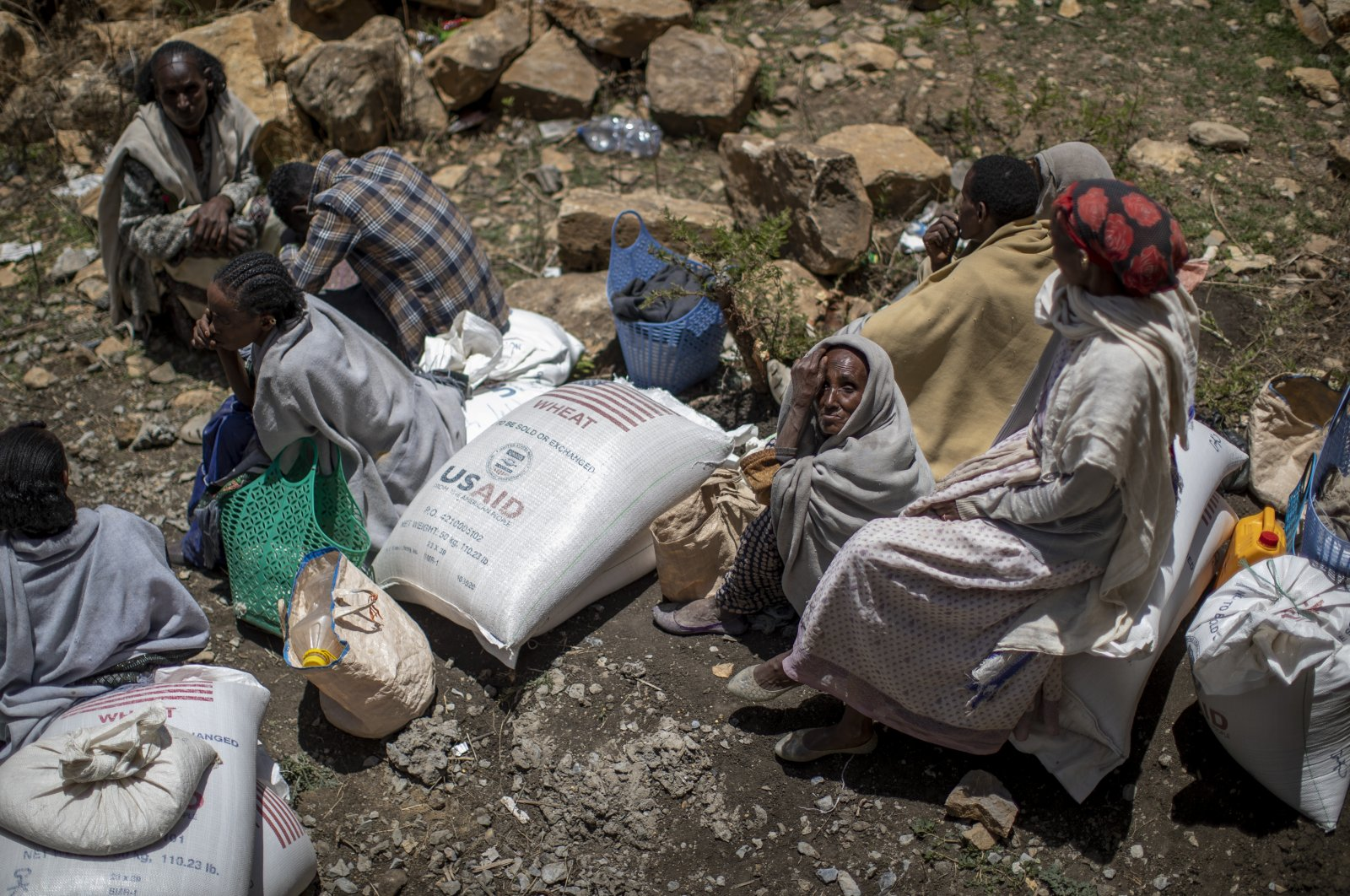 An elderly Ethiopian woman sits next to a sack of wheat after it was distributed to her by the Relief Society of Tigray in the town of Agula, in the Tigray region of northern Ethiopia, May 8, 2021. (AP Photo)