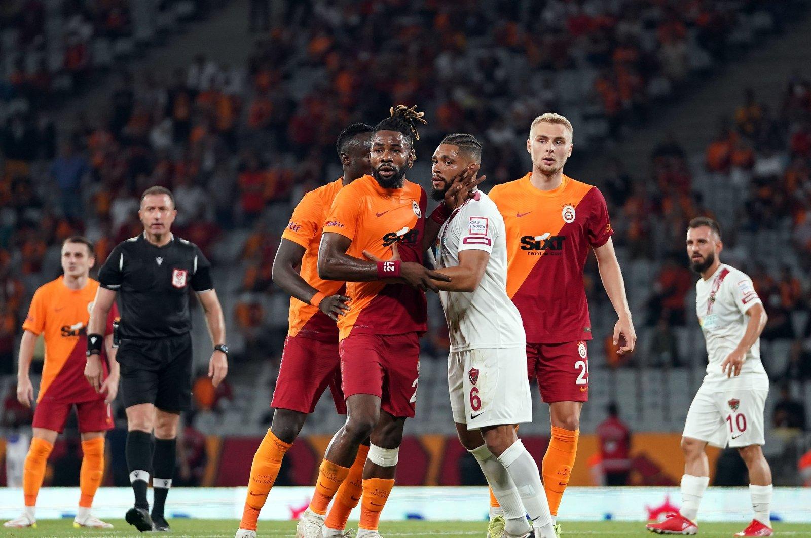 Galatasaray's Christian Luyindama (C) in action with Hatayspor's Jean-Claude Billong during the Turkish Süper Lig match at Istanbul's Atatürk Olympic Stadium, Turkey, Aug. 23, 2021 (IHA Photo)