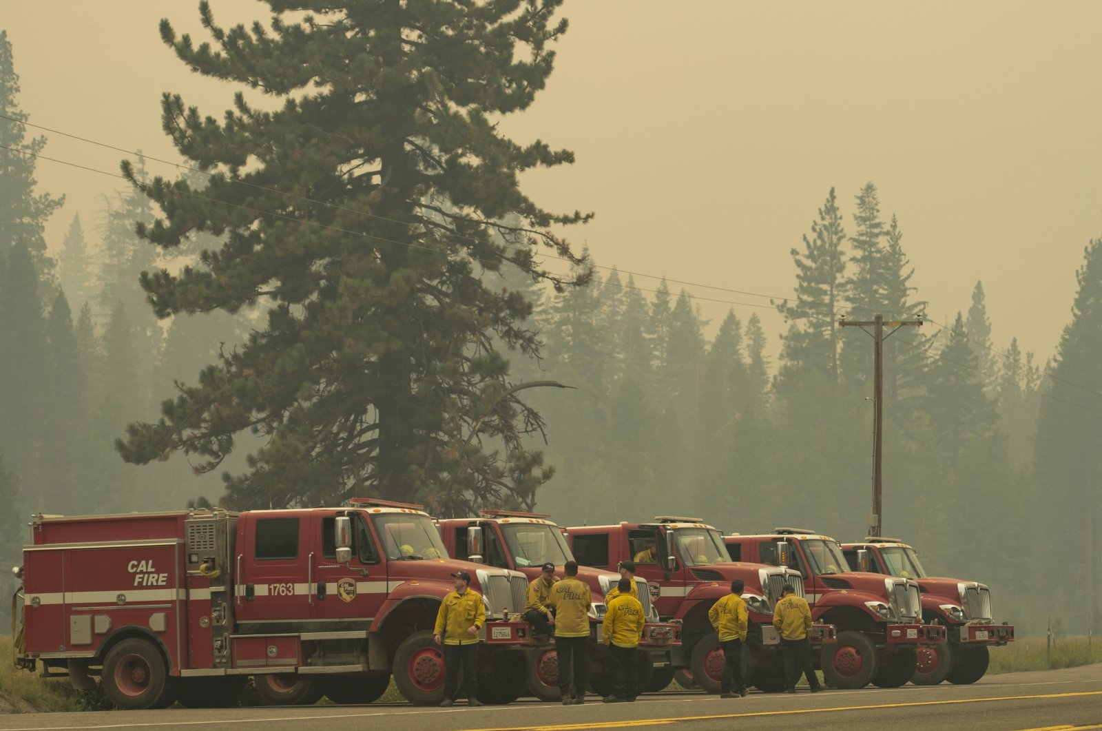 Cal Fire vehicles line up along Highway 50 in Strawberry, California, as smoke from the Caldor Fire burning on both sides of the route fills the air, Calif, U.S., Sunday, Aug. 22, 2021. (Sara Nevis / The Sacramento Bee via AP)