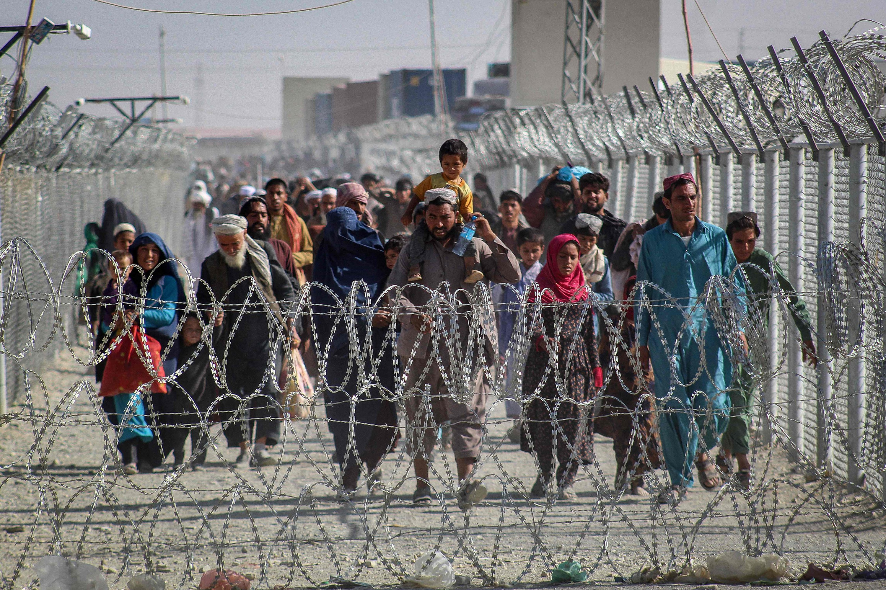 Afghans walk along fences as they arrive in Pakistan through the Pakistan-Afghanistan border crossing point following the Taliban's military takeover of Afghanistan, Chaman, Pakistan, Aug. 24, 2021. (AFP Photo)