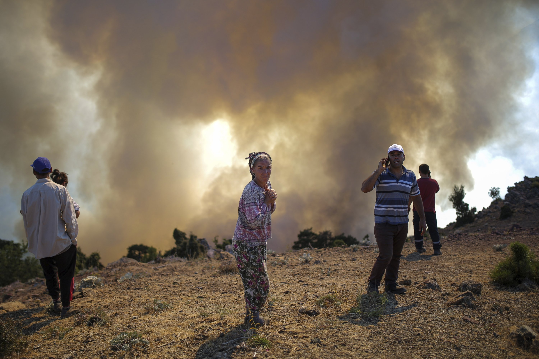 People watch a wildfire in Köyceğiz, Muğla, Turkey, Aug. 9, 2021. (AP Photo)