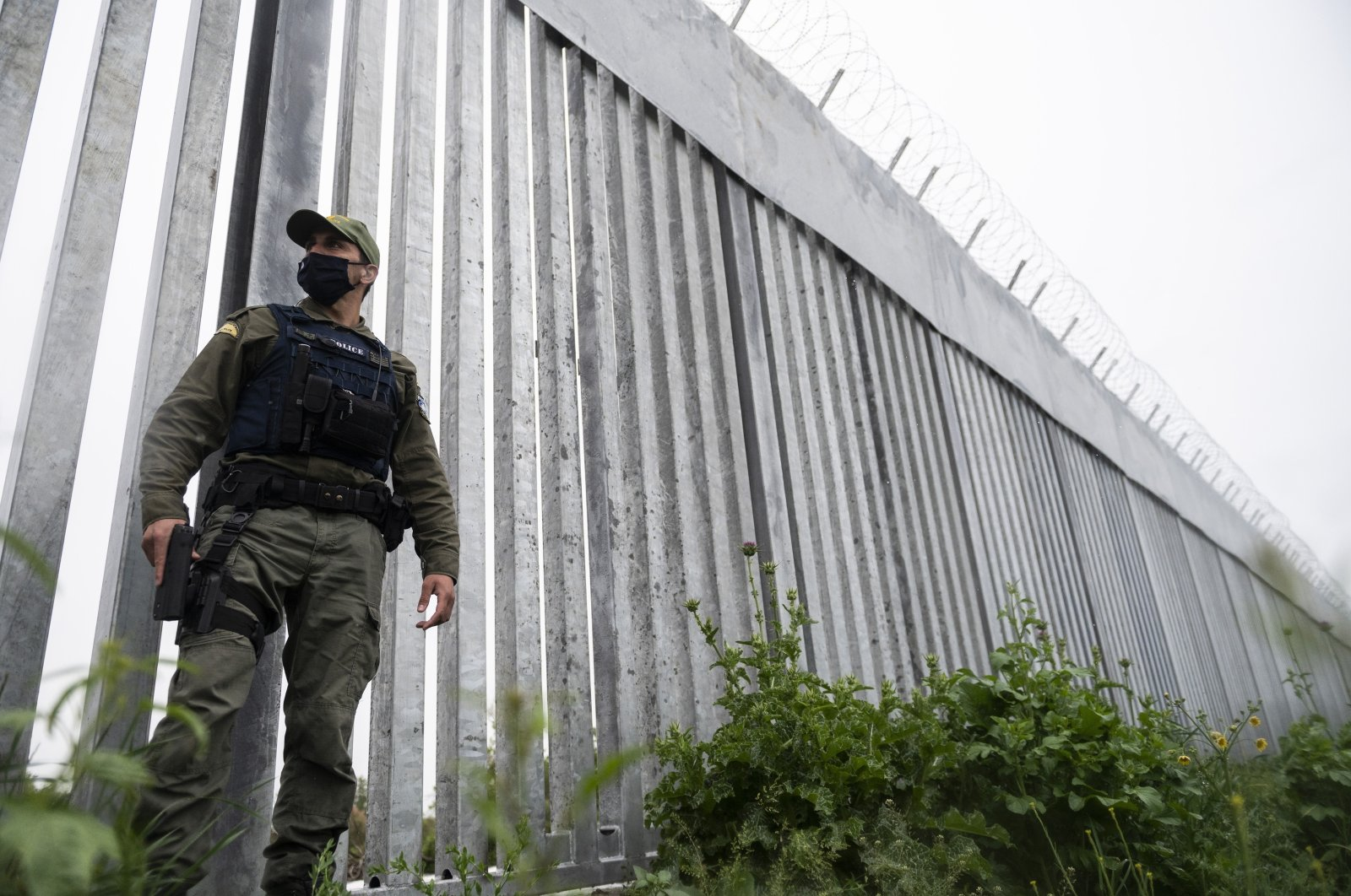 A police officer patrols alongside a steel wall at Evros river, near the village of Poros, at the Greek -Turkish border, Greece, May 21, 2021. (AP Photo)
