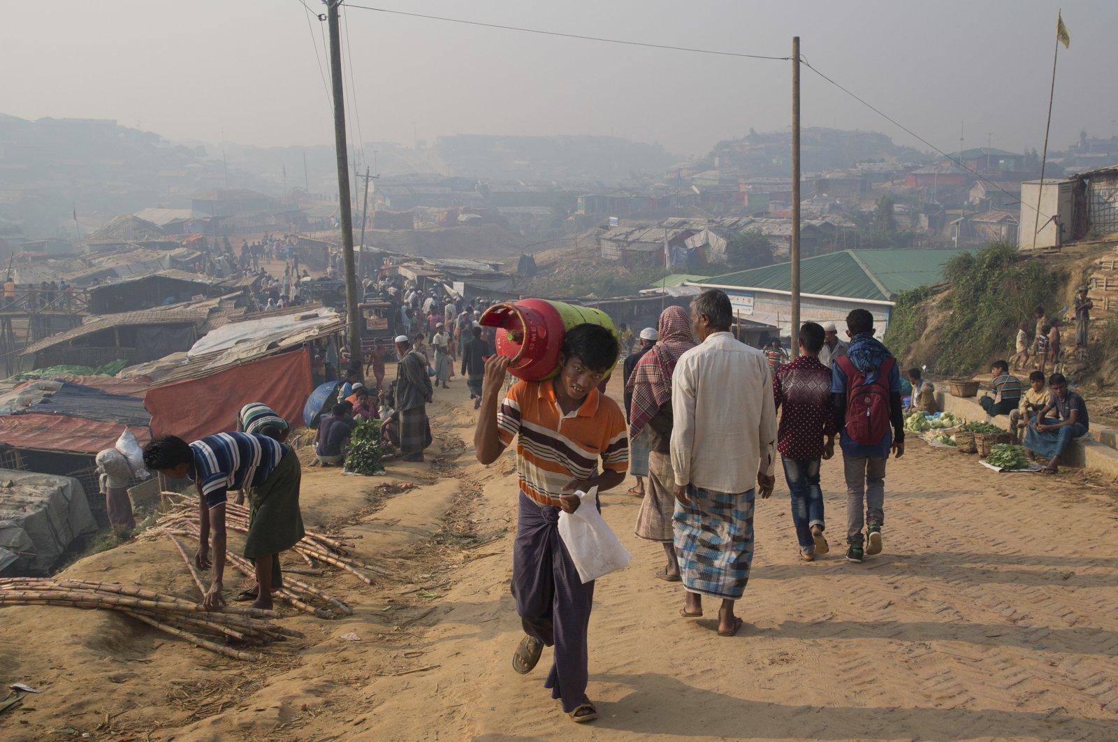 A Rohingya refugee walks carrying a cooking gas cylinder inside Balukhali refugee camp near Cox's Bazar in Bangladesh, Nov. 17, 2018. (AP Photo)