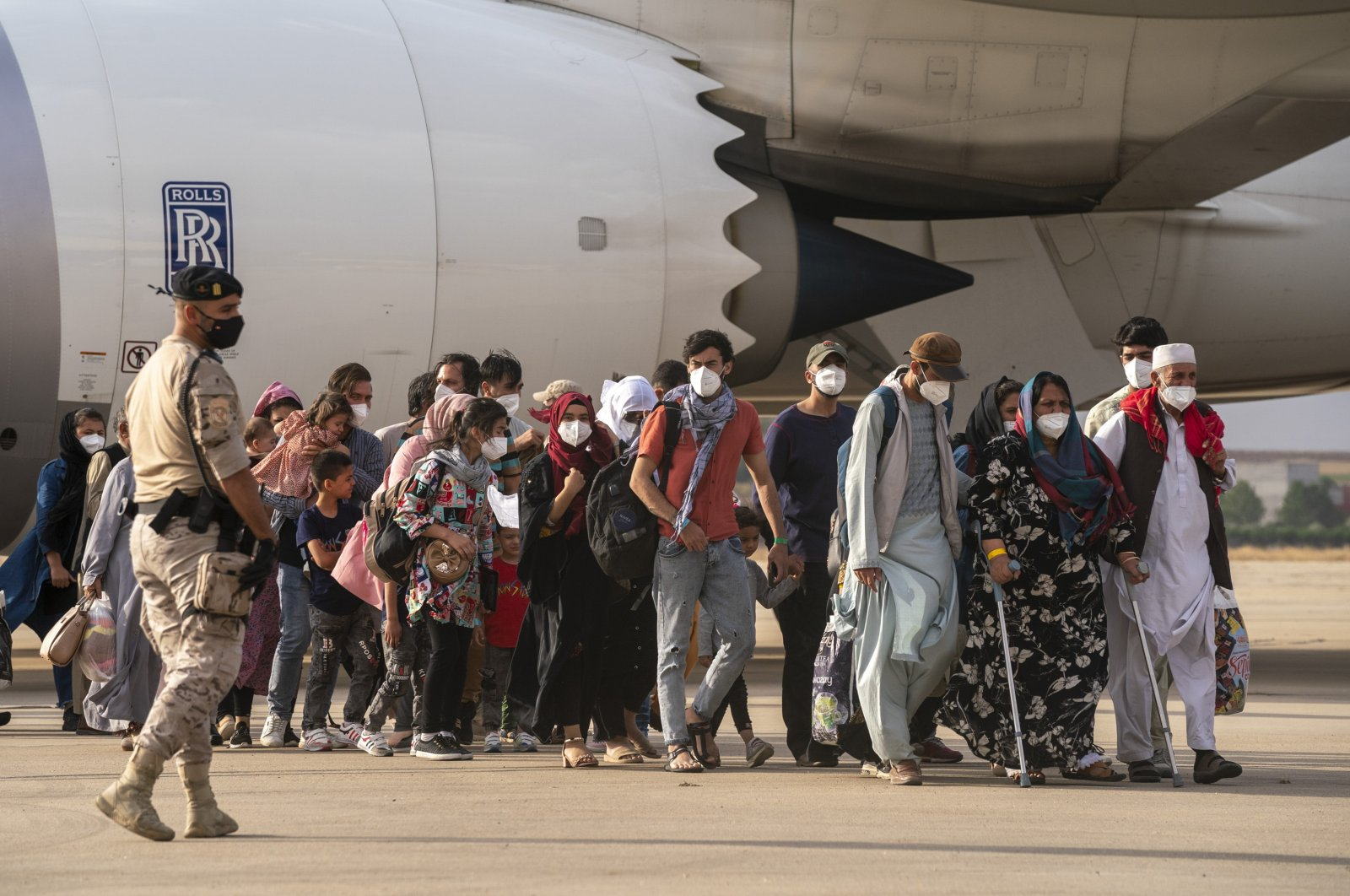 Afghan people pass a Spanish soldier after arriving on a plane at the Torrejon military base as part of the evacuation process from Afghanistan, Madrid, Spain, Aug. 23, 2021. (AP Photo)