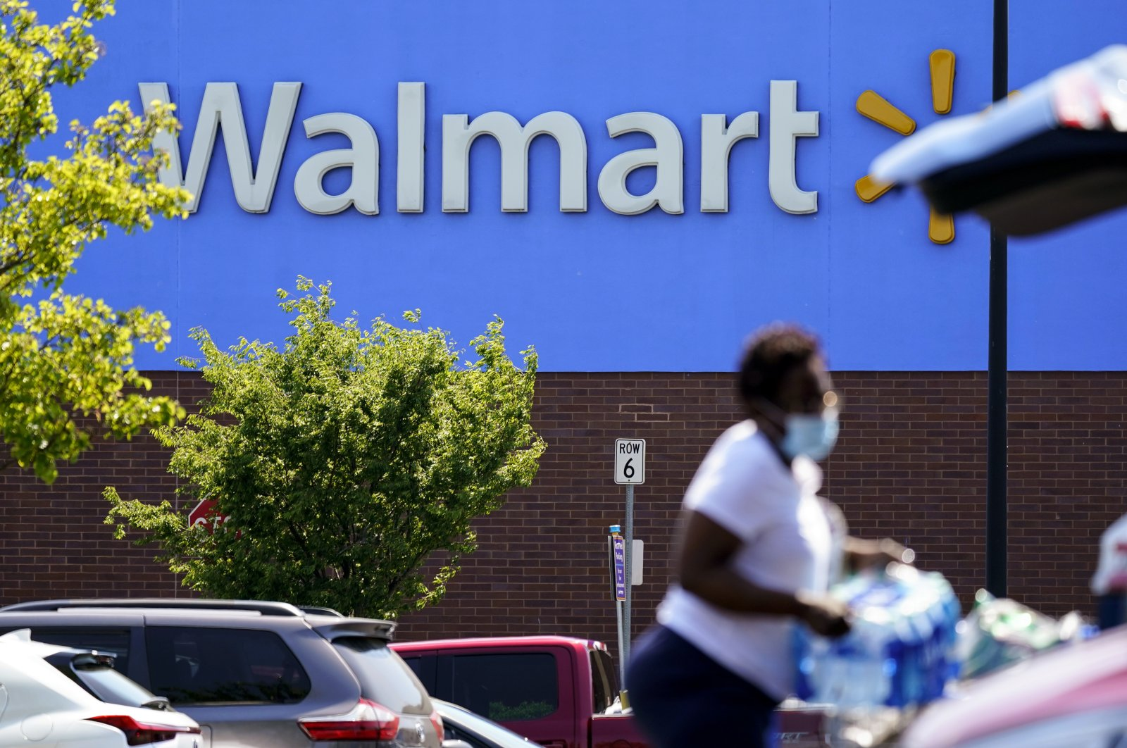 A shopper loads items into her car in the parking lot of a Walmart in Willow Grove, Pennsylvania, U.S., May 19, 2021. (AP Photo)