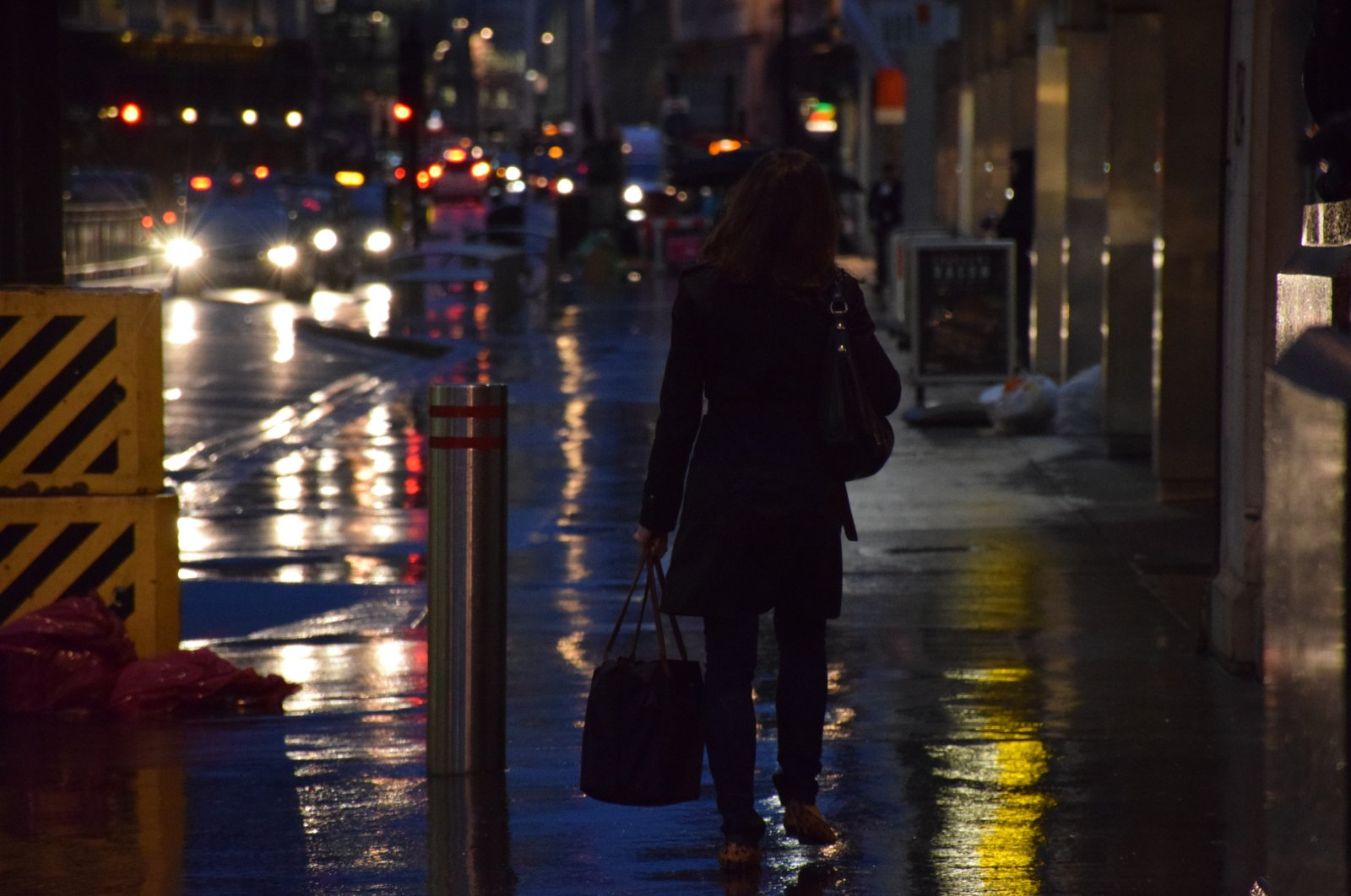 A woman walks on a wet sidewalk in a city at night. (Getty Images)