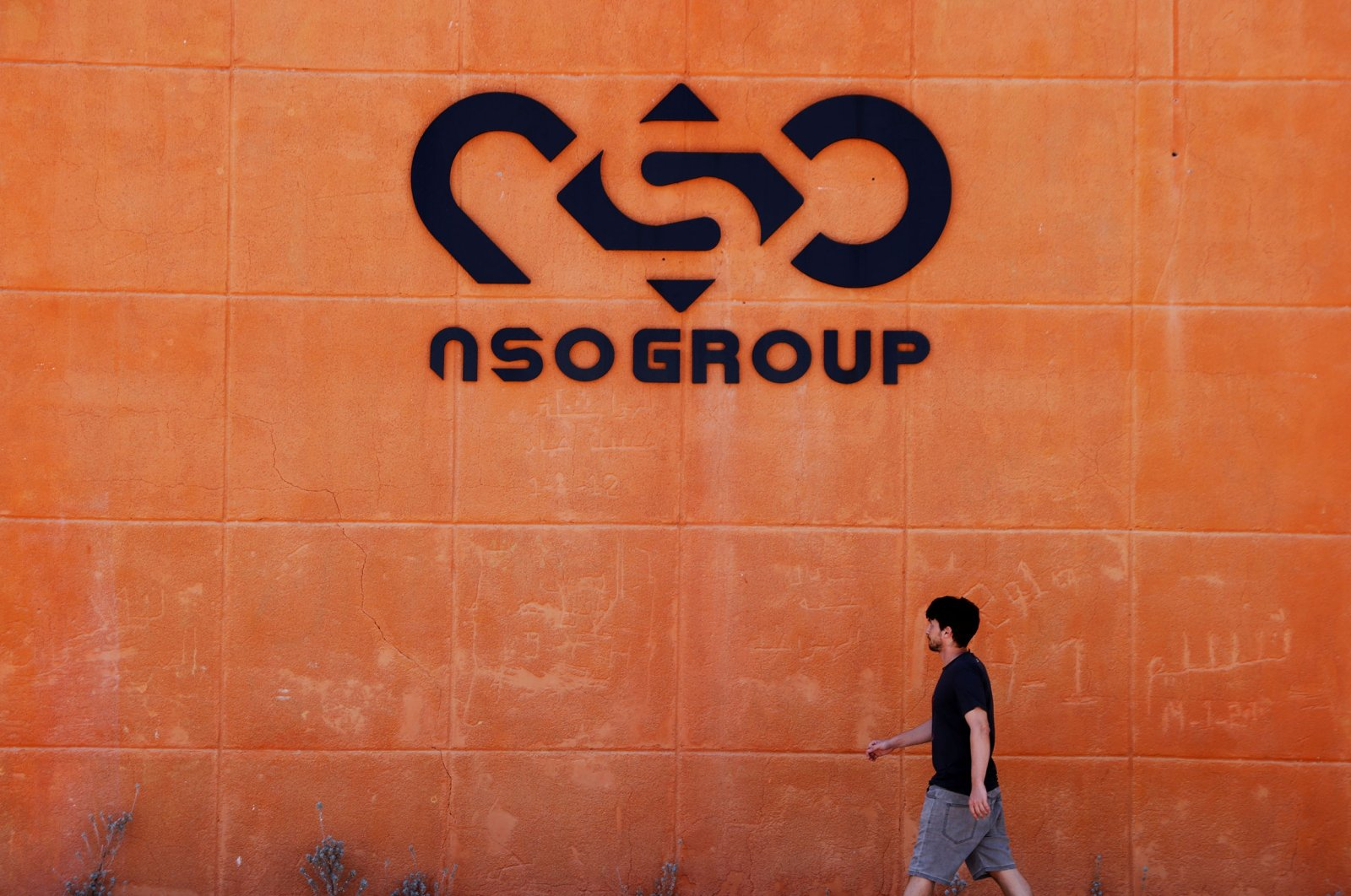 A man walks past the logo of Israeli cyber firm NSO Group at one of its branches in the Arava Desert, southern Israel, July 22, 2021. (Reuters Photo)