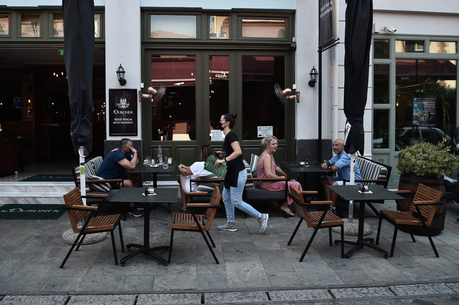 People sit at a pub in the center of Thessaloniki, Greece,  Aug. 24, 2021. (AFP Photo)