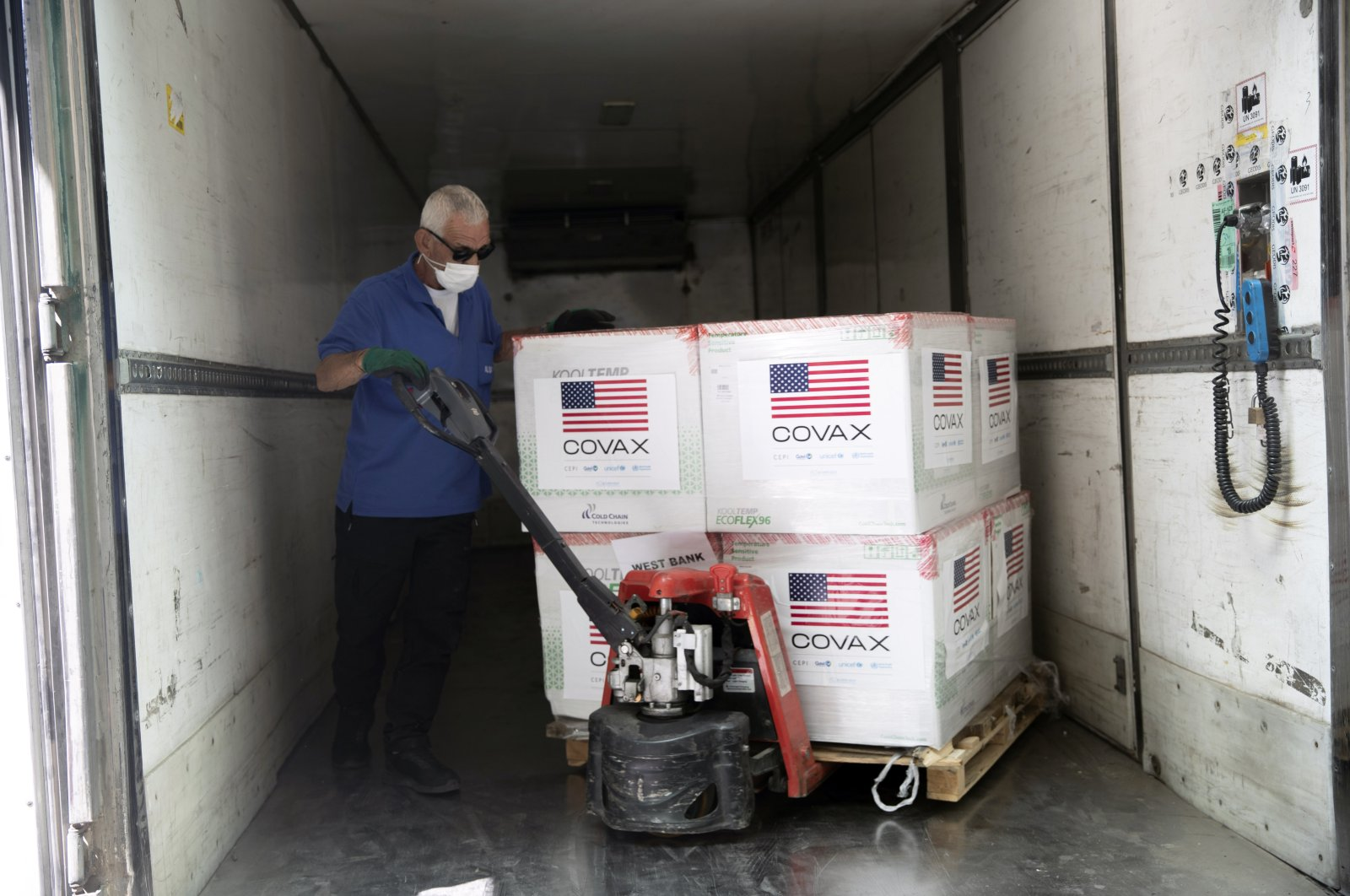 Palestinians unload a shipment of the Moderna coronavirus vaccine donated by the U.S, at the Palestinian health ministry, in the West Bank village of Salem, near Nablus, Aug. 24, 2021. (AP Photo)
