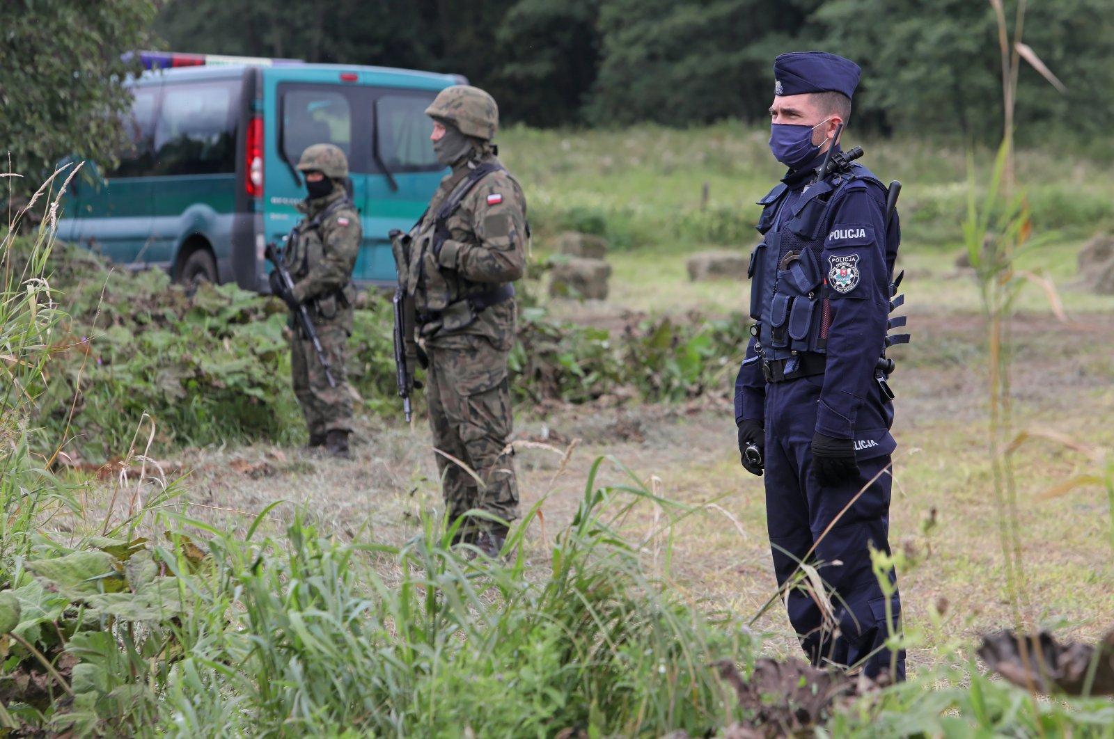 Polish police and border guards stand at the Polish-Belarusian border near Usnarz Gorny village, northwestern Poland, Aug. 24, 2021. (EPA Photo)
