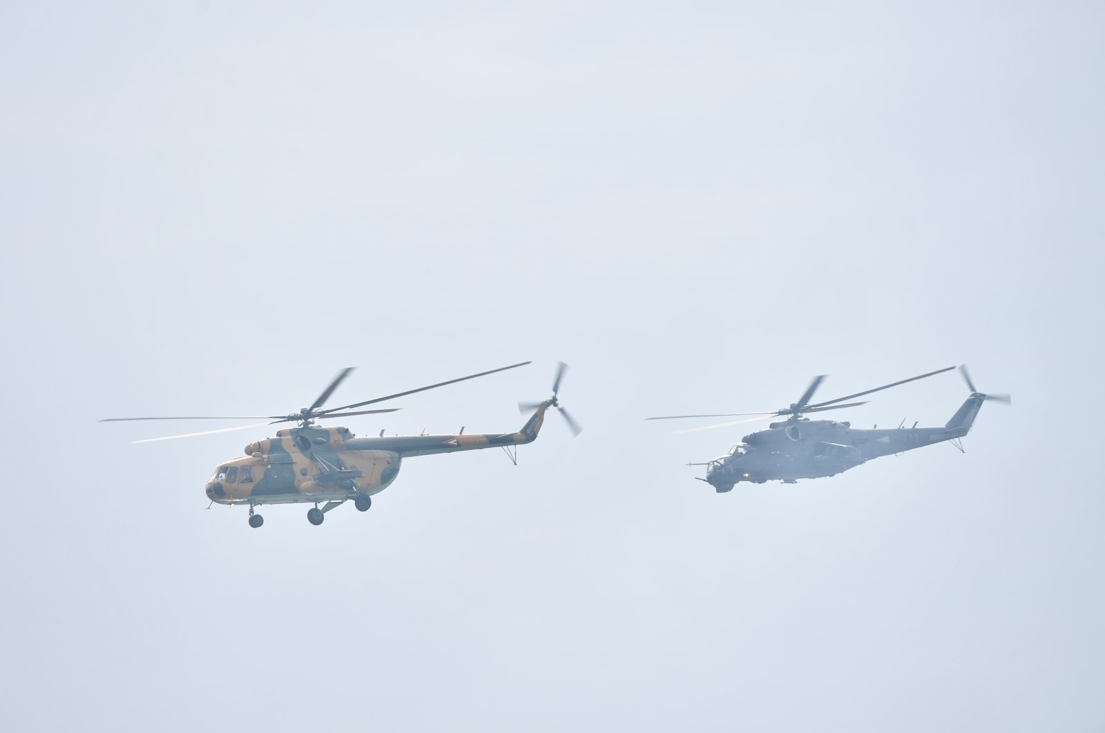 The Hungarian Air Force's Mi-17 transport helicopter (left) and a Mi-24 fighter helicopter fly low during the St. Stephen's Day celebration in Budapest, Hungary, Aug. 20, 2021. (Reuters Photo)