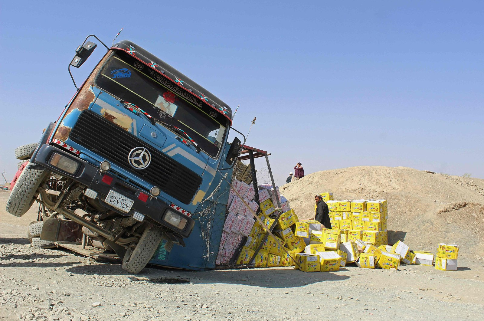 An Afghan driver stands amid boxes of dry food next to his damaged truck at the site of an accident near the Pakistan-Afghanistan border crossing point in Chaman, Pakistan, on Aug. 20, 2021. (AFP Photo)