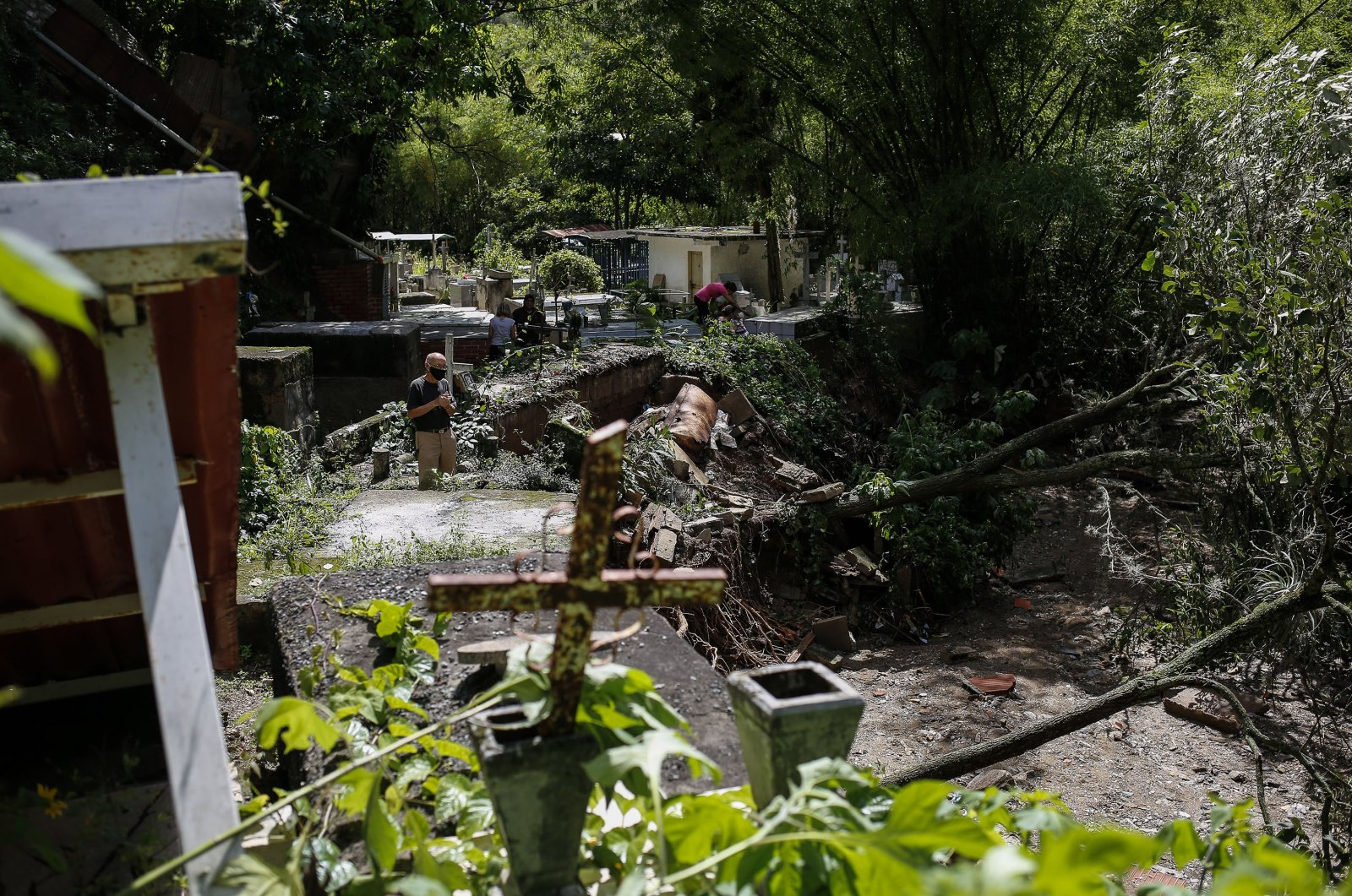 A man watches the damage at a public cemetery after heavy rain caused flooding the previous day in Los Angelinos Canyon, Venezuela, June 25, 2021. (Getty Images)