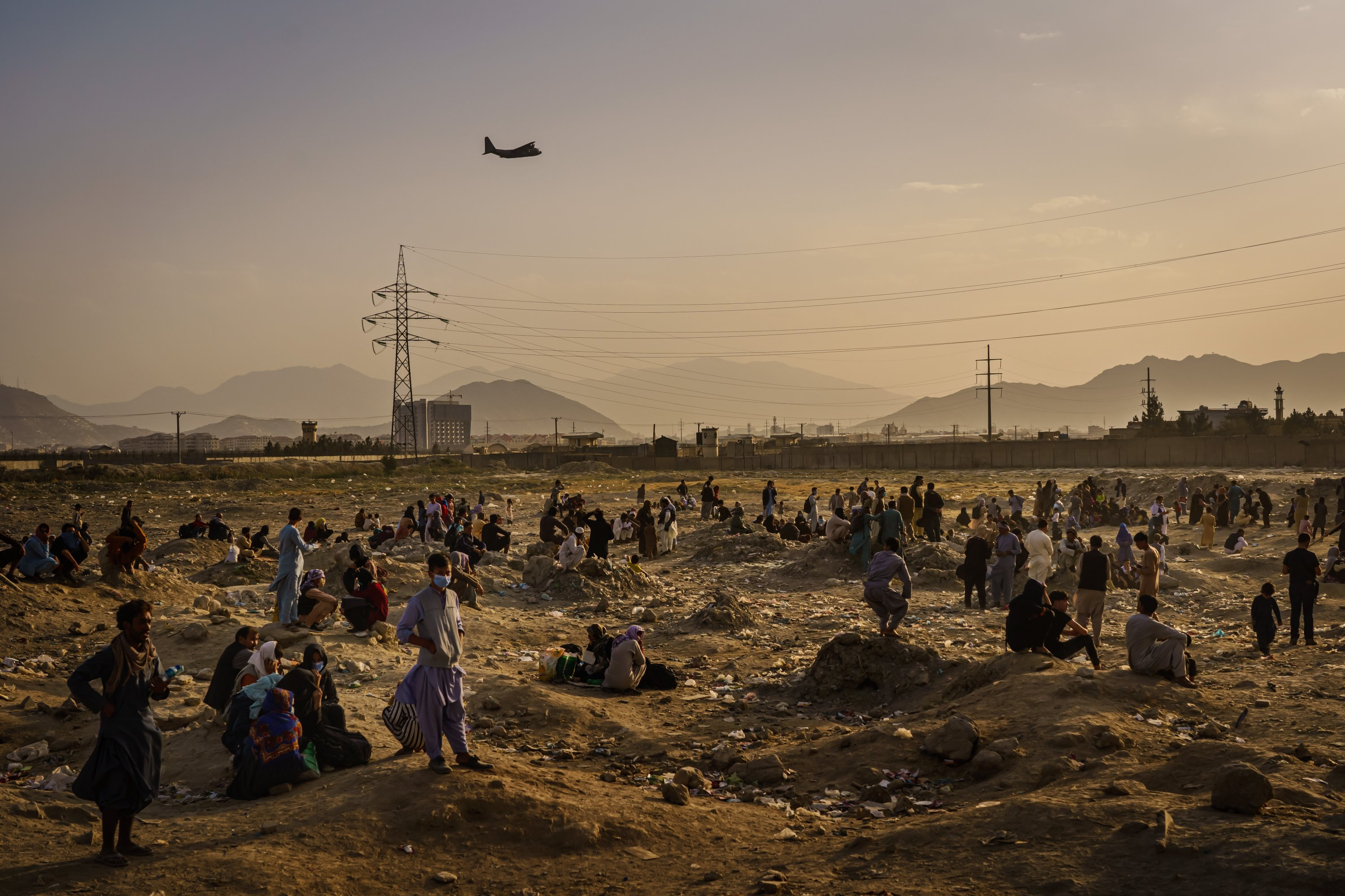 A military transport plane takes off while Afghans who cannot get into the airport to evacuate, watch and wonder while stranded outside, in Kabul, Afghanistan, Aug. 23, 2021. (Photo by Getty Images)