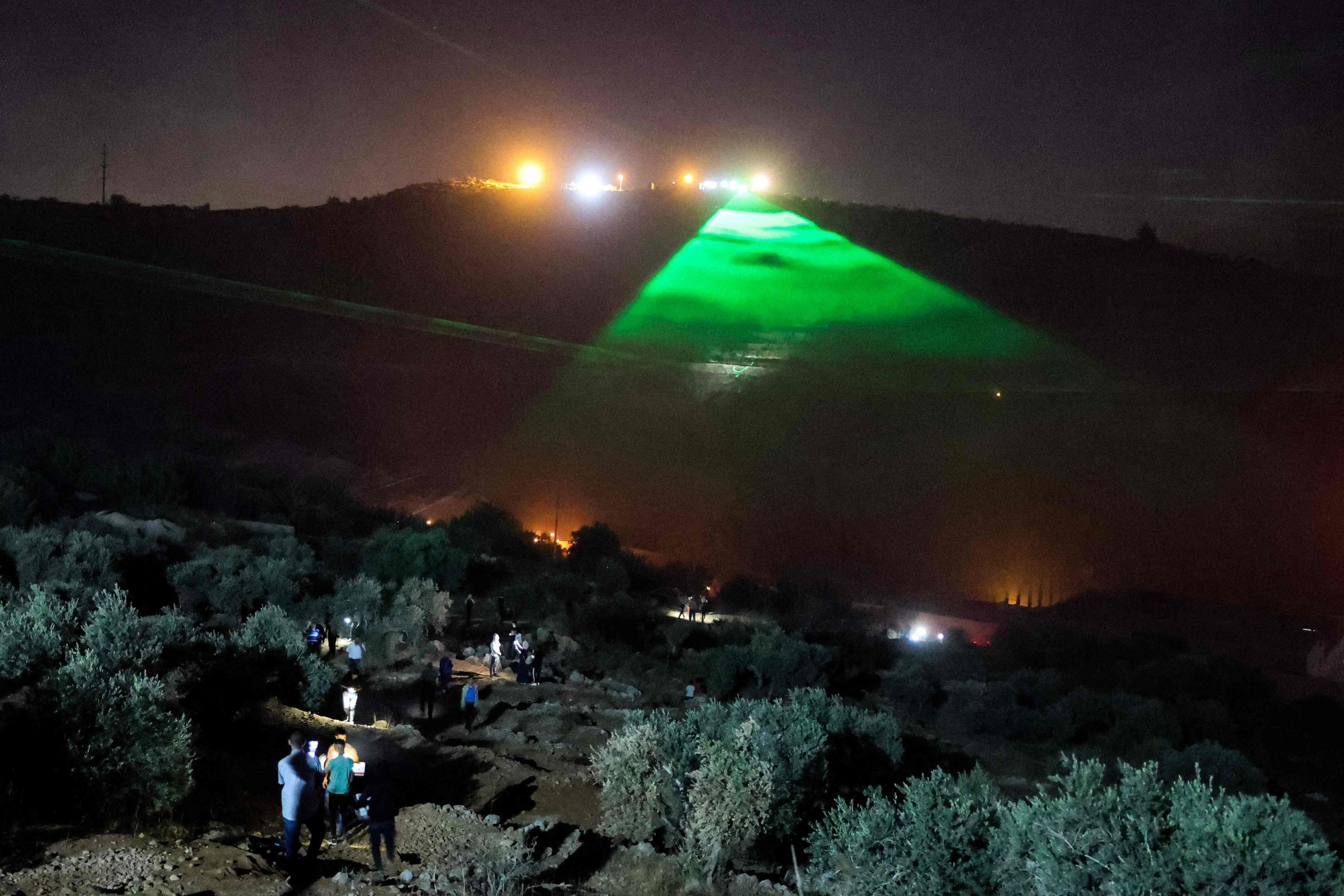 Palestinian protesters use laser torches during a demonstration against the Israeli settlers' outpost of Eviatar,  in the town of Beita, occupied West Bank, Palestine, June 30, 2021. (AFP Photo)