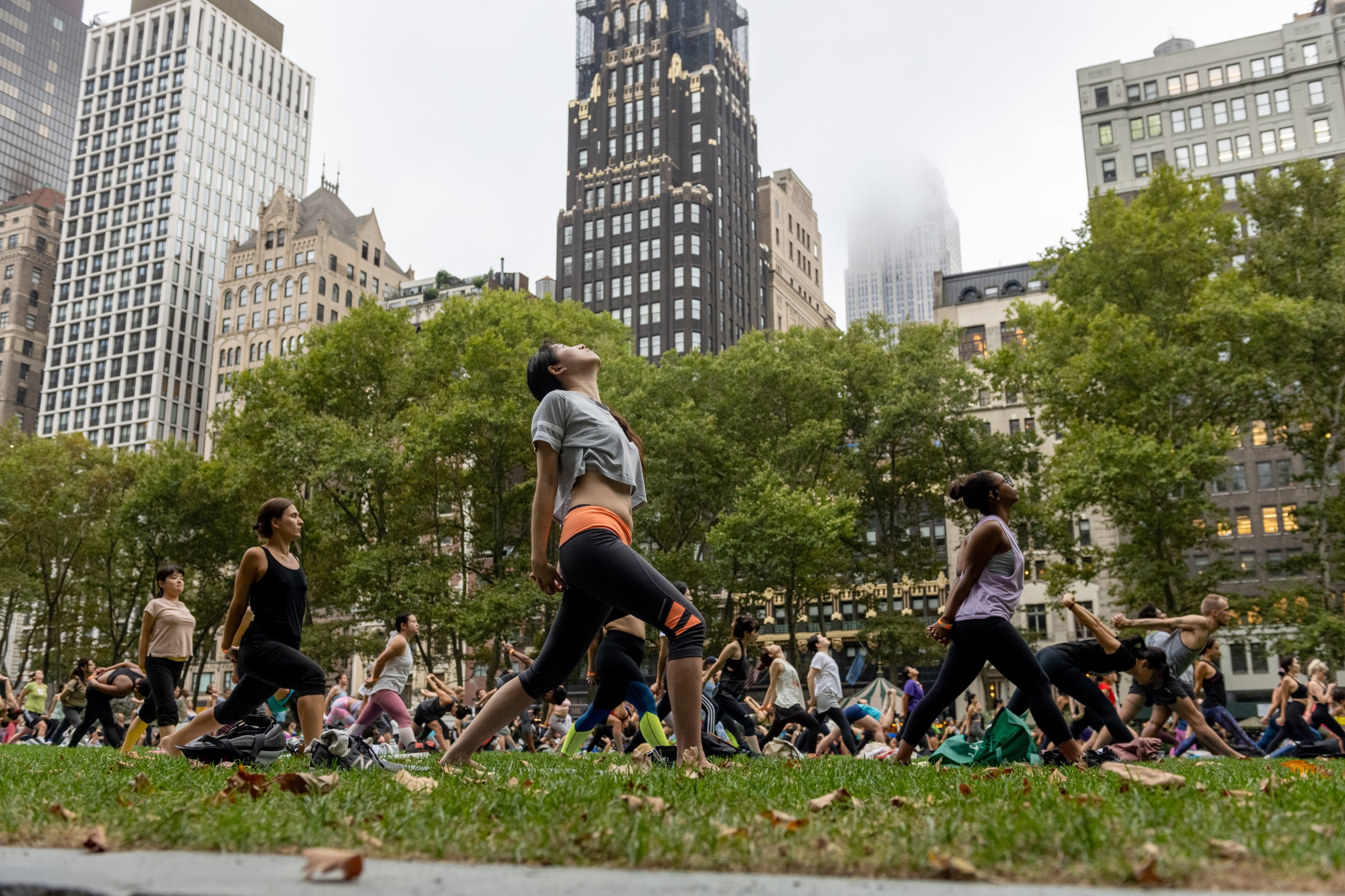 People do yoga on the grass in Bryant Park with a view of the Empire State Building in the background, in New York City, New York, U.S., Aug. 18, 2021. (Photo by Getty Images)