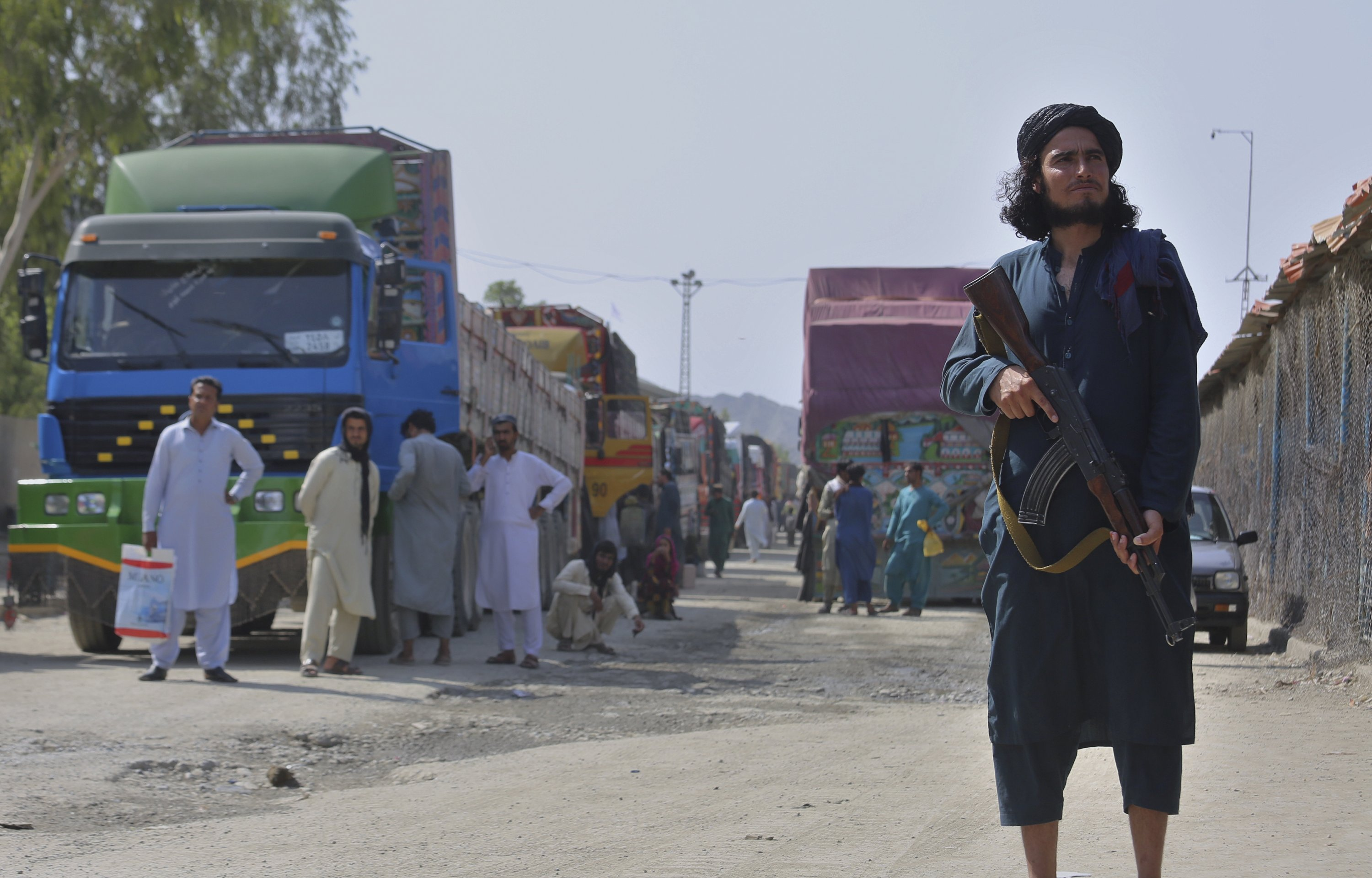 A Taliban fighter stands guard on the Afghan side while people wait to cross at a border crossing point between Pakistan and Afghanistan, in Torkham, in Khyber district, Pakistan, Aug. 21, 2021. (AP Photo)