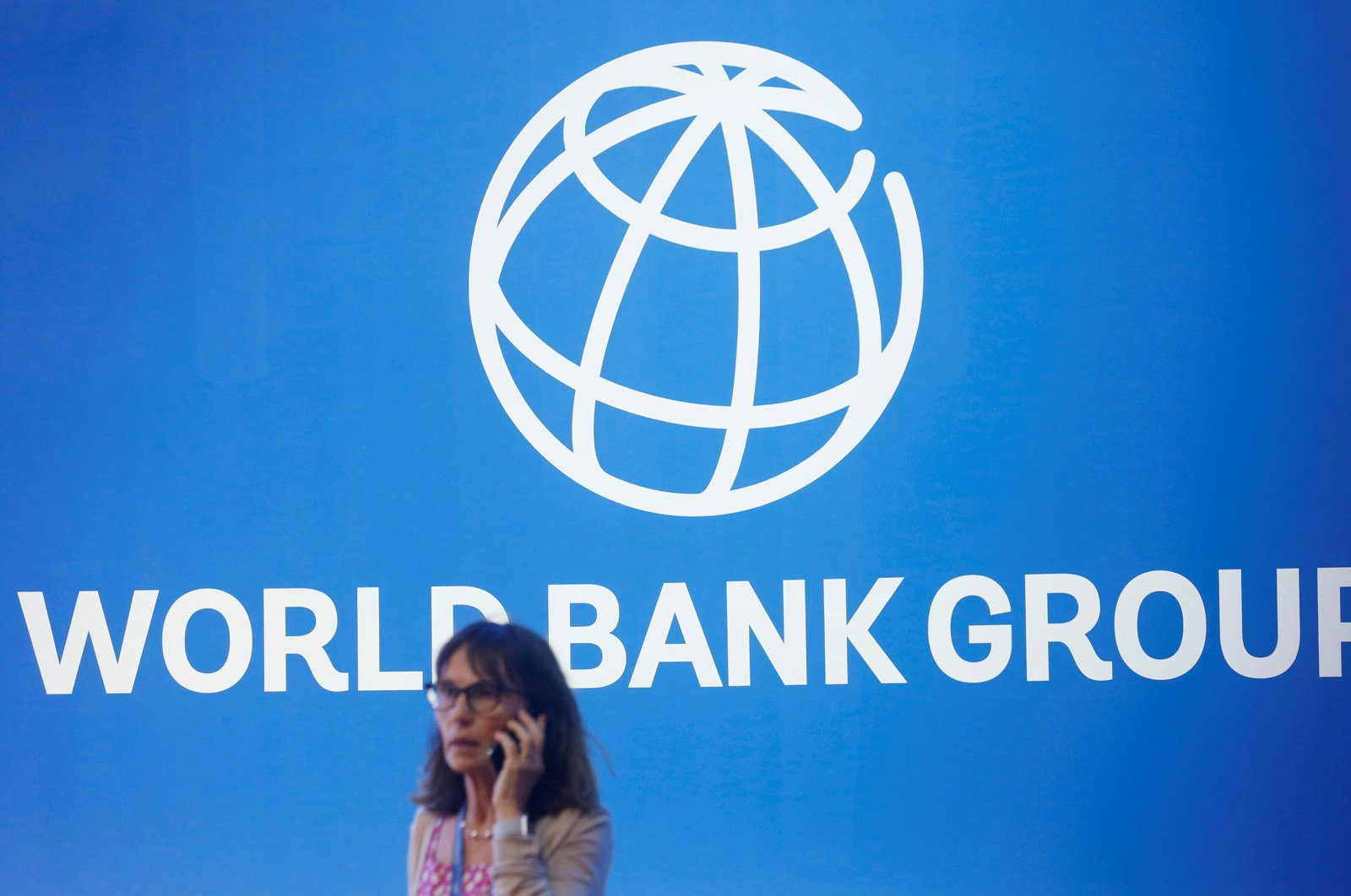 A participant stands near a logo of the World Bank at the International Monetary Fund - World Bank Annual Meeting 2018 in Nusa Dua, Bali, Indonesia, Oct. 12, 2018. (Reuters File Photo)