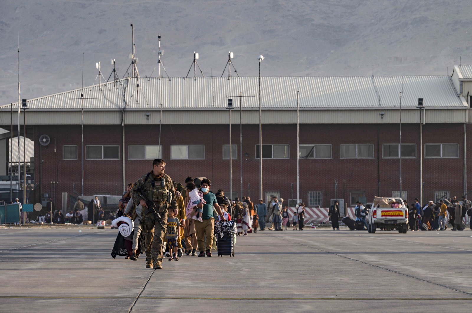A U.S. Air Force officer guides evacuees to board a U.S. Air Force C-17 Globemaster III at Hamid Karzai International Airport in Kabul, Afghanistan, Aug. 24, 2021. (AP Photo)
