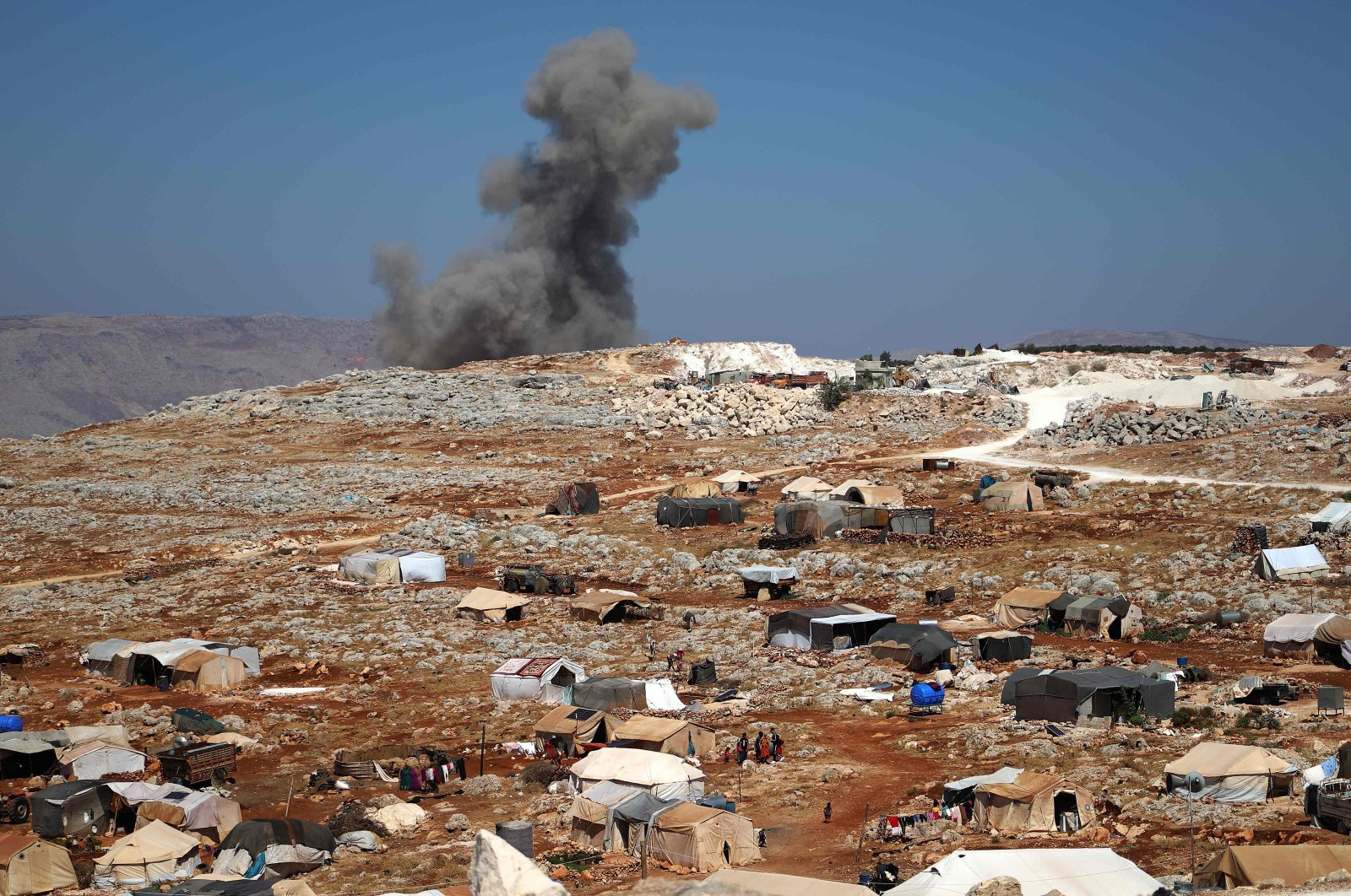 A plume of smoke rises behind a hill, where internally displaced Syrians have set up tents, during reported airstrikes by pro-regime forces, north of the opposition-held city of Idlib, Syria, Aug. 20, 2021. (AFP Photo)