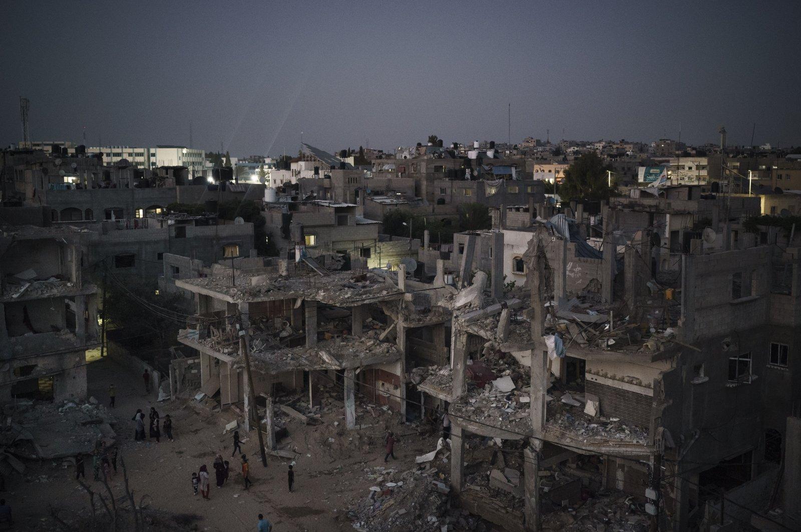 Palestinians walk at night along Al-Baali Street, next to homes heavily damaged by airstrikes during an 11-day war between Israel and Hamas in Beit Hanoun, northern Gaza Strip, Palestine, May 31, 2021. (AP Photo)
