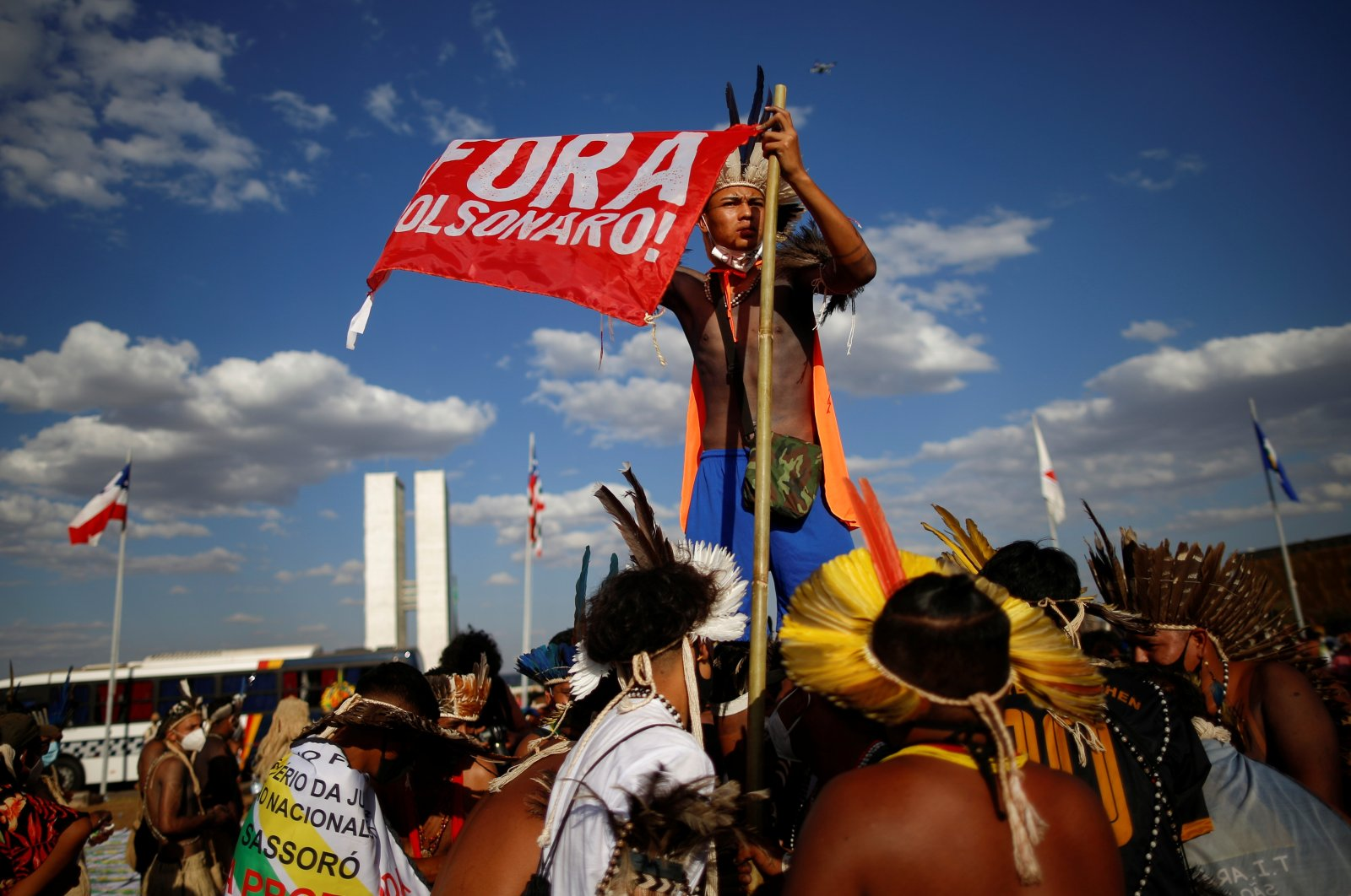 """An Indigenous Brazilian holds a banner reading """"Bolsonaro out"""" during a protest for land demarcation and against President Jair Bolsonaro's government, near the National Congress in Brasilia, Brazil, Aug. 24, 2021. (Reuters Photo)"""