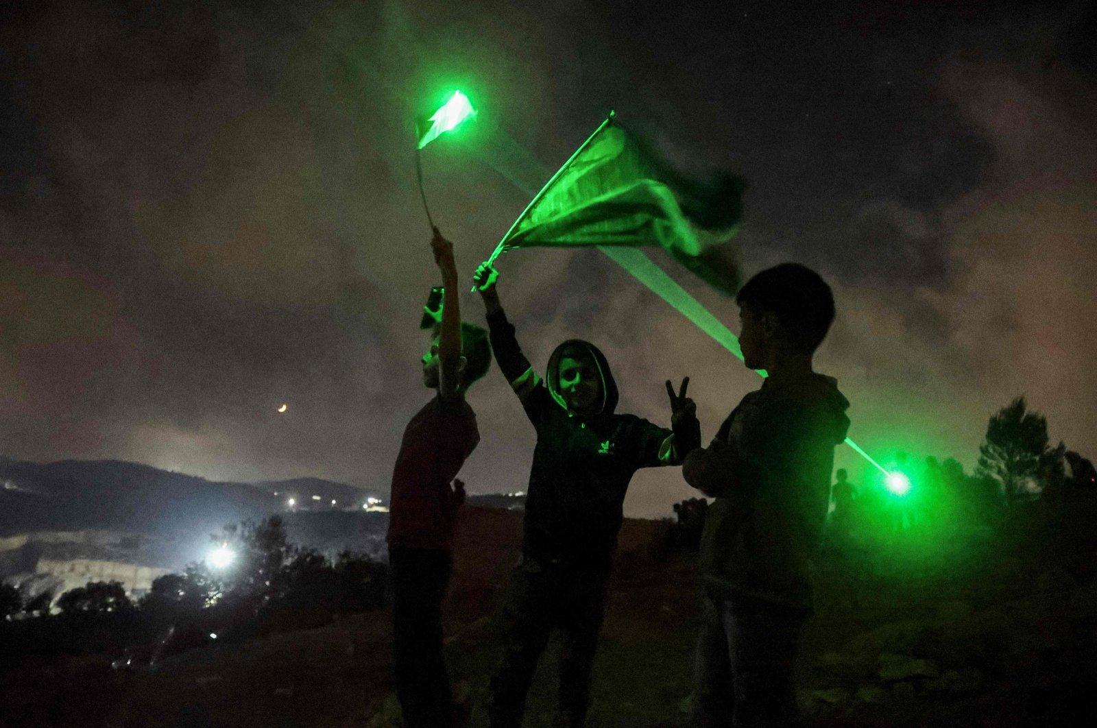 Young Palestinian protesters use laser torches during a demonstration against the Israeli settlers' outpost of Eviatar, in the town of Beita, occupied West Bank, Palestine, July 13, 2021. (AFP Photo)