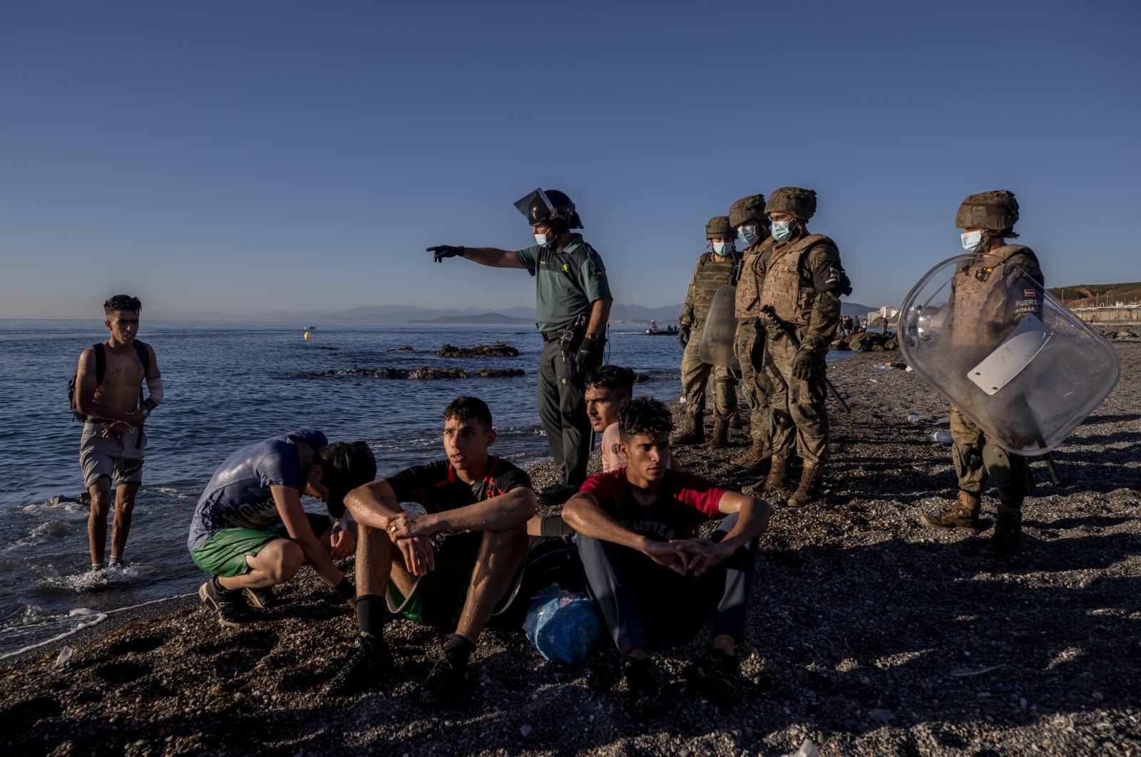 Migrants are surrounded by Spanish security forces on a beach after arriving at the Spanish enclave of Ceuta, near the border of Morocco and Spain, May 19, 2021. (AP Photo)