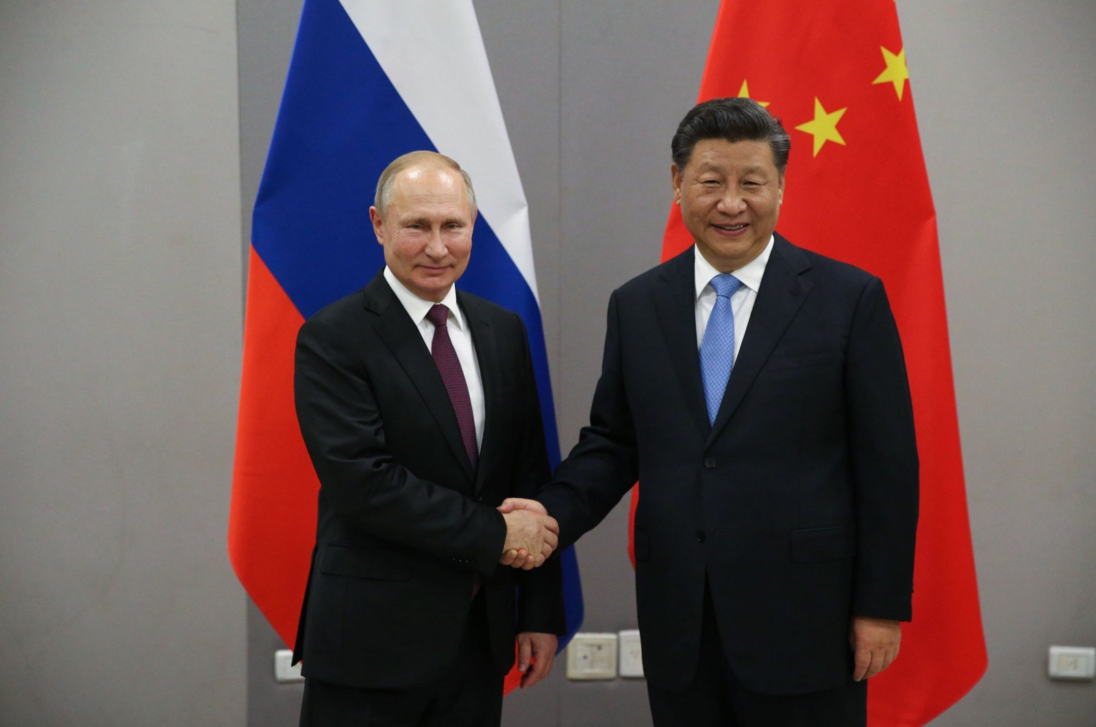 Russian President Vladimir Putin (L) greets Chinese President Xi Jinping (R) during their bilateral meeting, Nov. 13, 2019, in Brasilia, Brazil. (Getty Images)