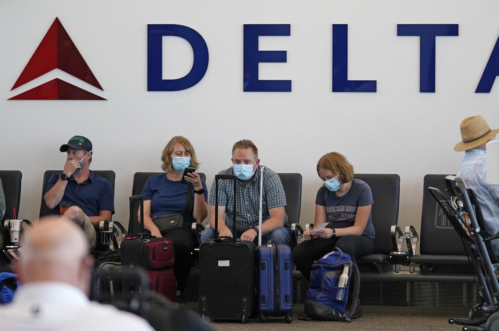 People sit under a Delta sign at Salt Lake City International Airport in Salt Lake City, U.S., July 1, 2021. (AP Photo)