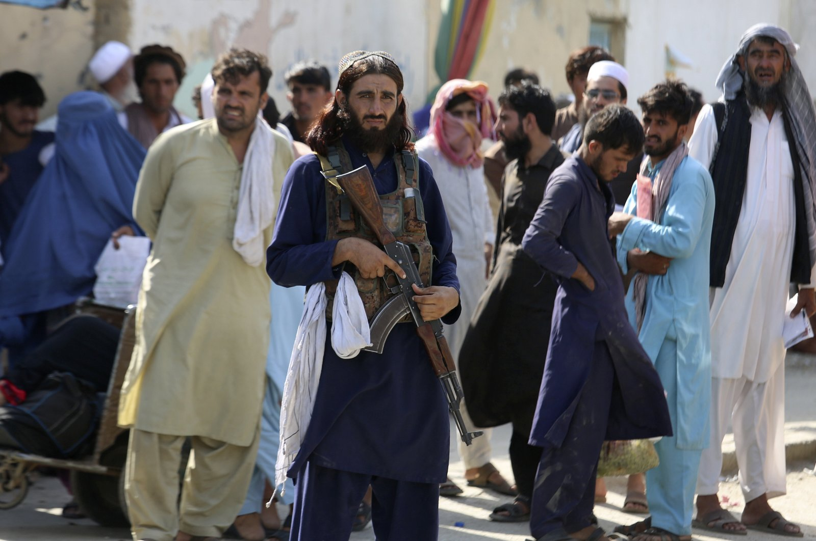 A Taliban fighter stands guard on Afghan side while people wait to cross at a border crossing point between Pakistan and Afghanistan, in Torkham, in Khyber district, Pakistan, Aug. 21, 2021. (AP Photo)