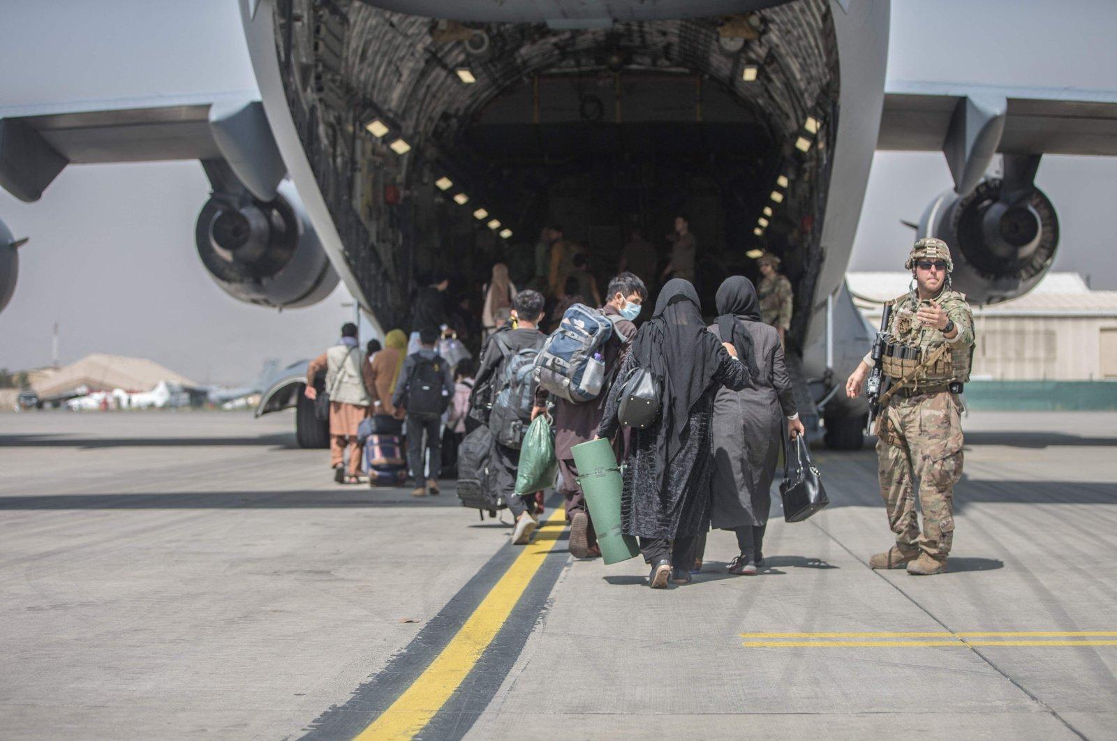 Families begin to board a U.S. Air Force Boeing C-17 Globemaster III during an evacuation at Kabul Hamid Karzai International Airport, Kabul, Afghanistan, Aug. 23, 2021. (U.S. Marine Corps via AFP Photo)