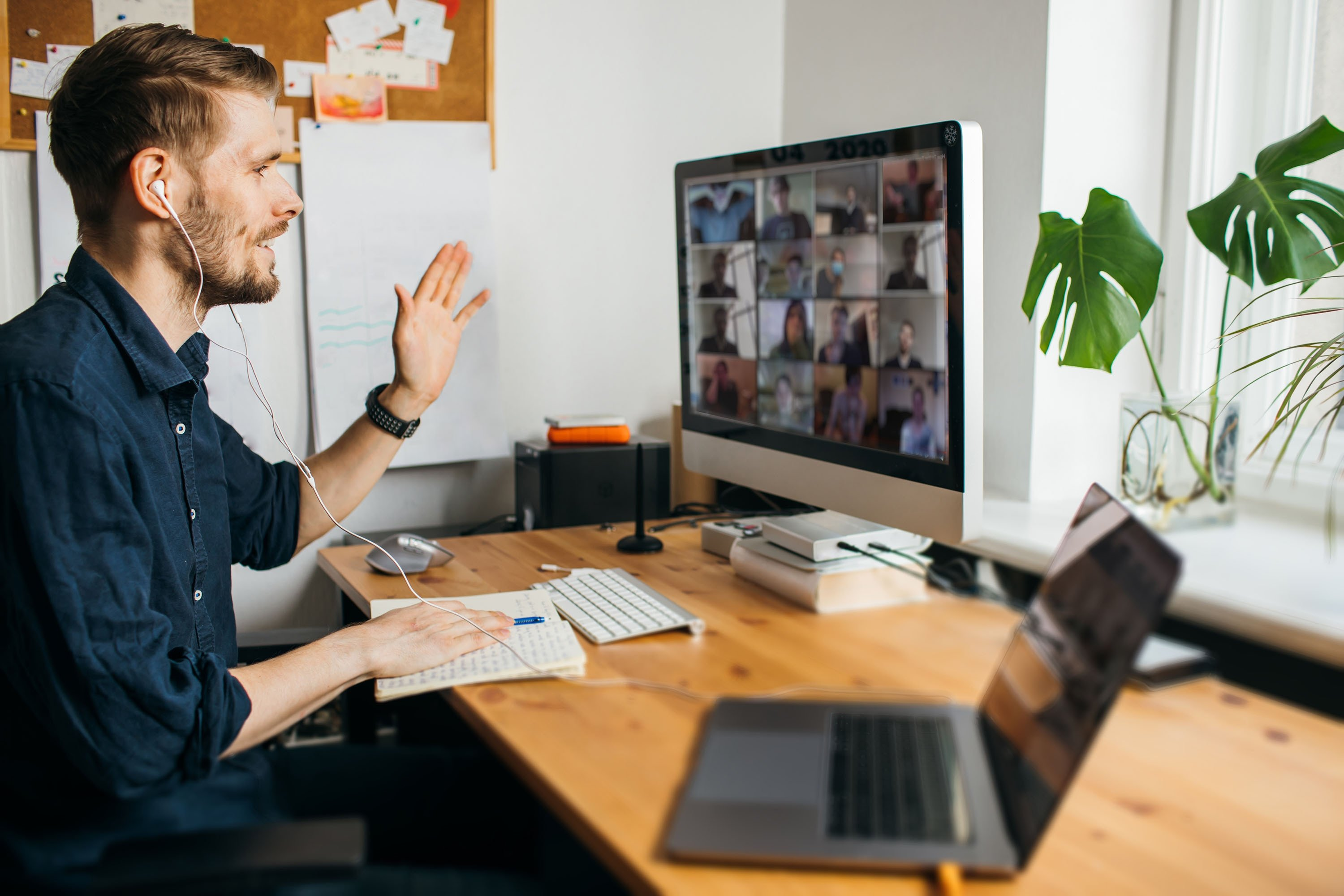 A young professional conducts a video call from his home office. (Shutterstock Photo)