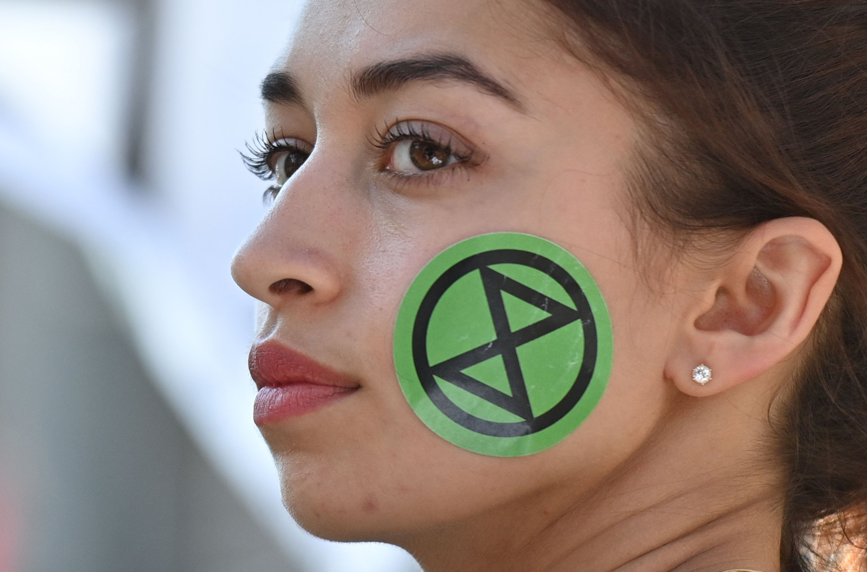 A climate activists from the Extinction Rebellion group wears a sticker on her face as she joins others in blocking the road in the middle of Oxford Circus in central London, U.K., on Aug. 25, 2021. (AFP Photo)